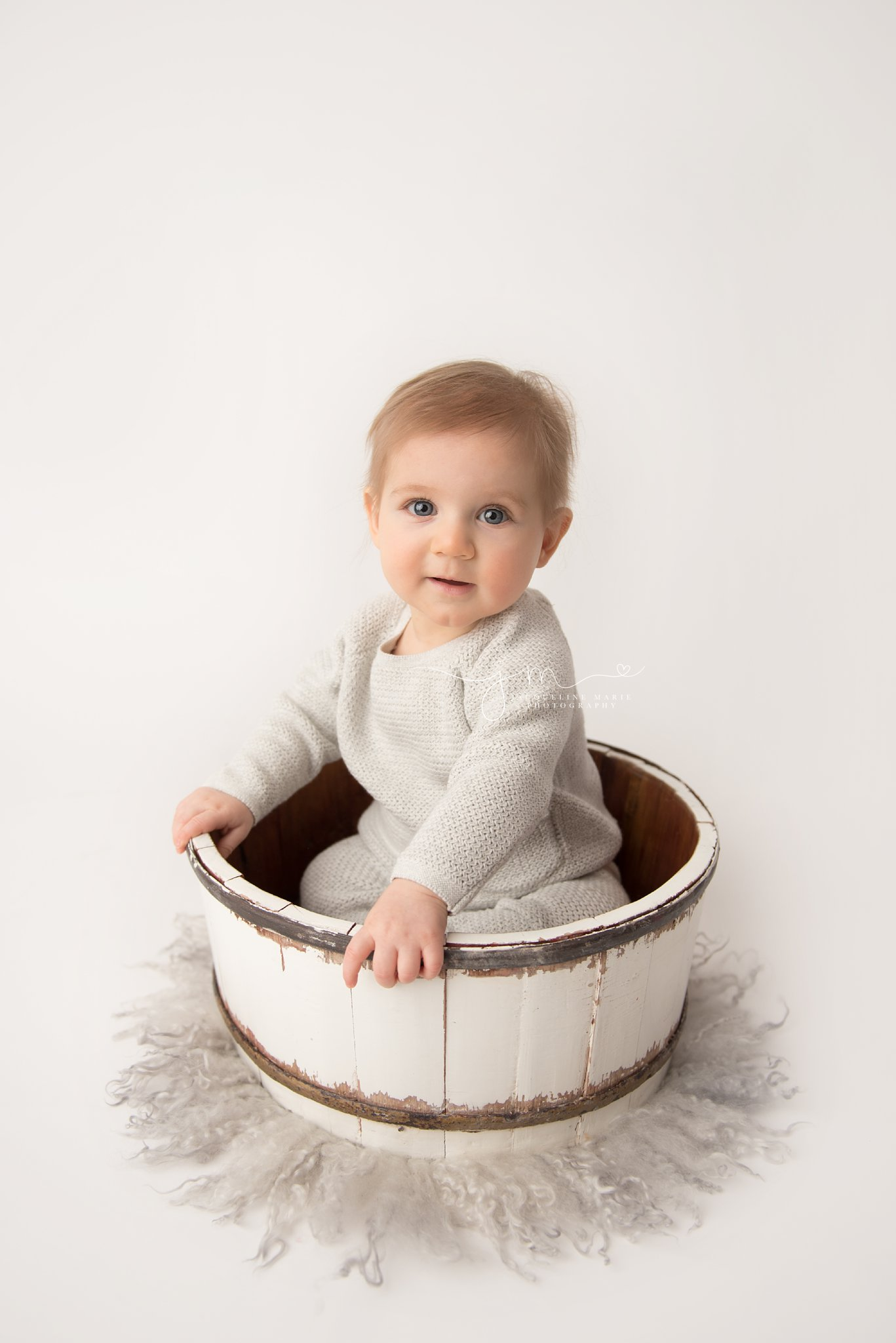 6 month old bay boy wears gray sweater and pants in a white wooden bowl in columbus ohio baby photographer studio