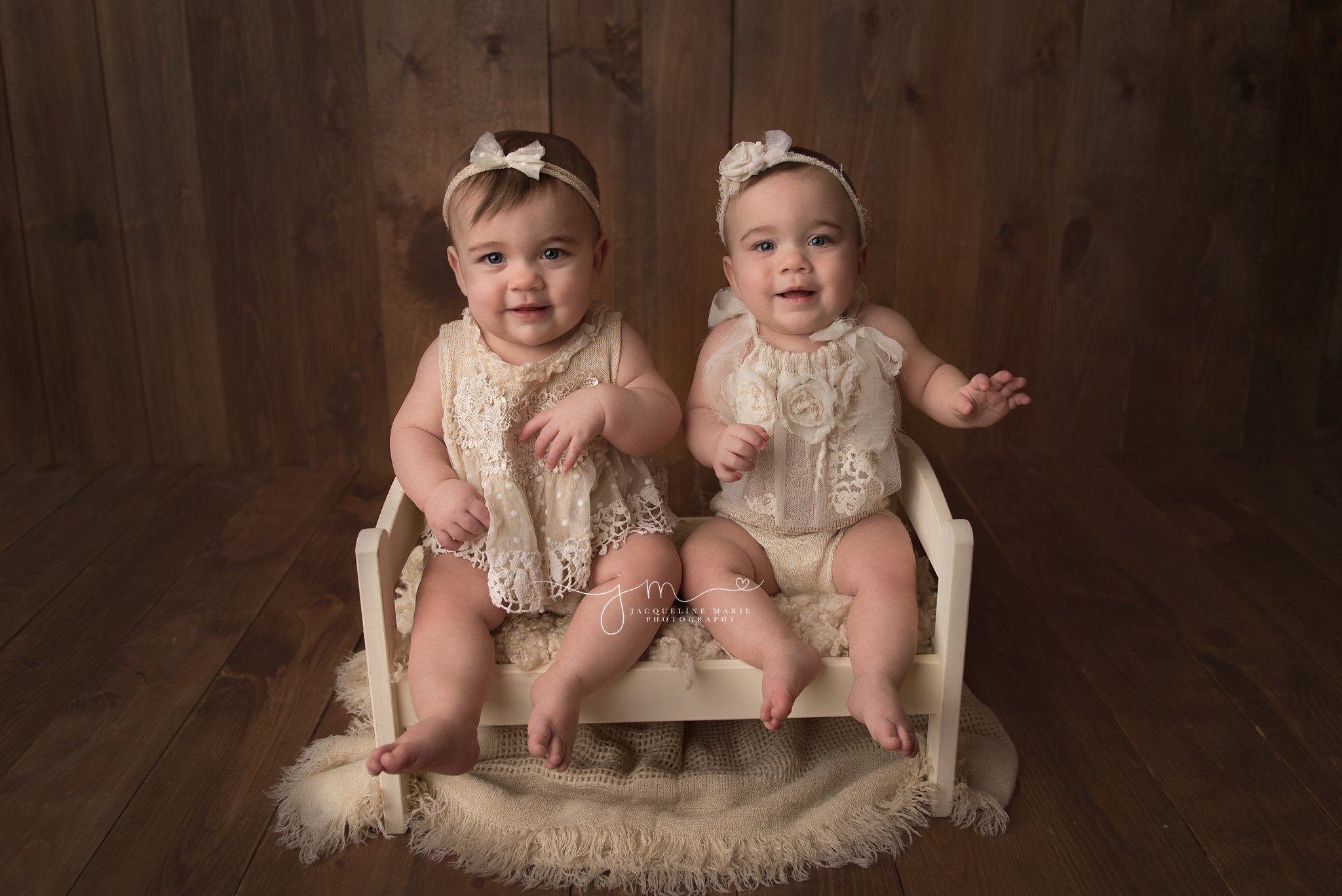 1 year old sisters sit on cream wooden bed prop in columbus ohio for first birthday session