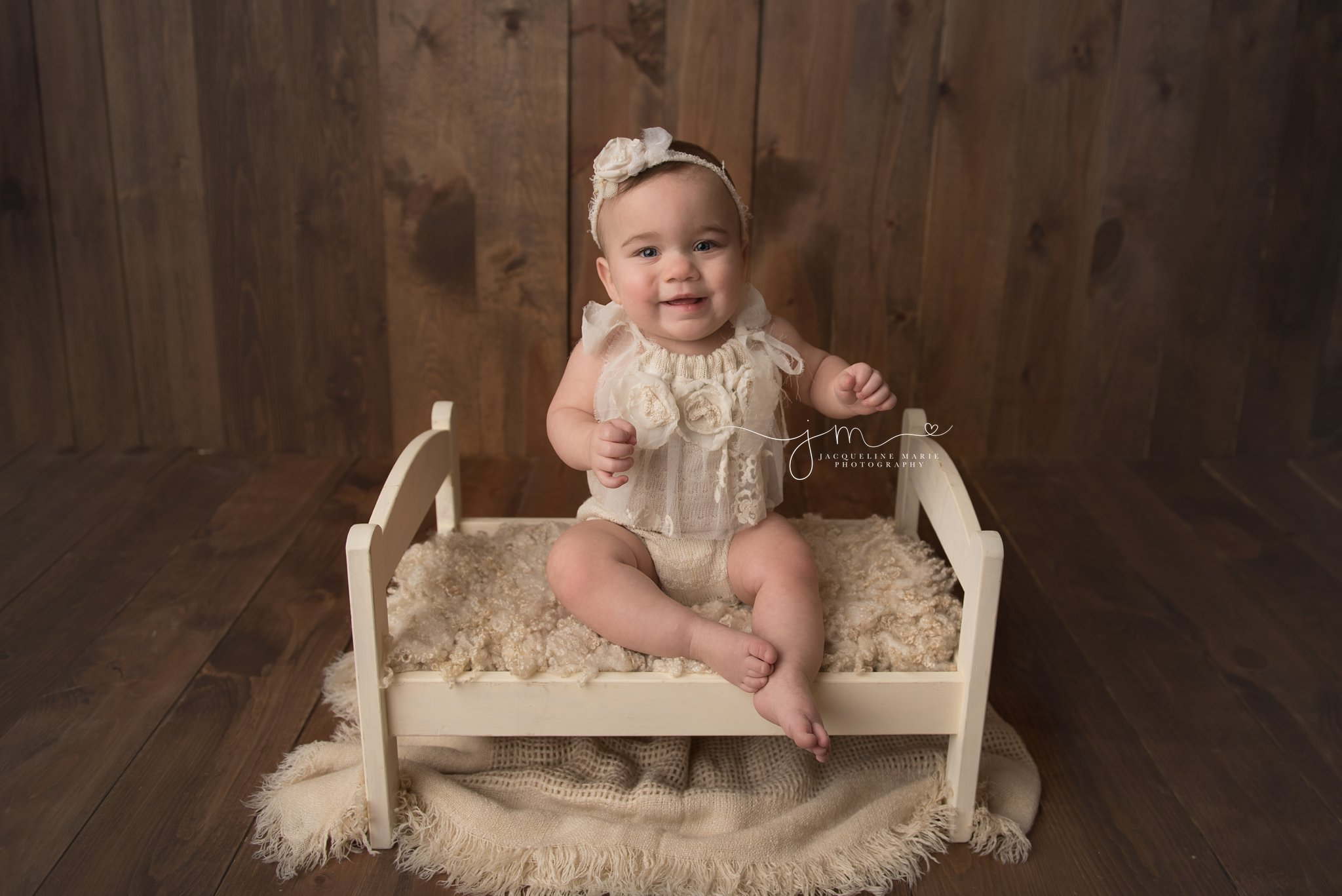 1 year old baby girl smiles wearing a cream romper for first birthday portraits in columbus ohio