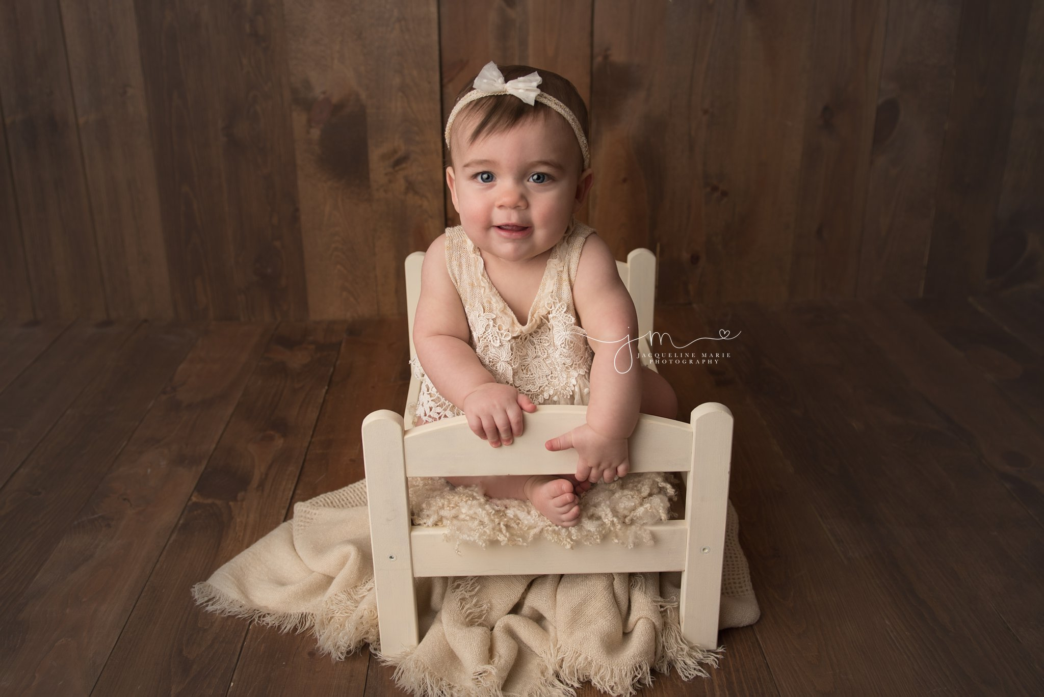 columbus ohio first birthday photographer features image of baby girl wearing cream bow for portrait session