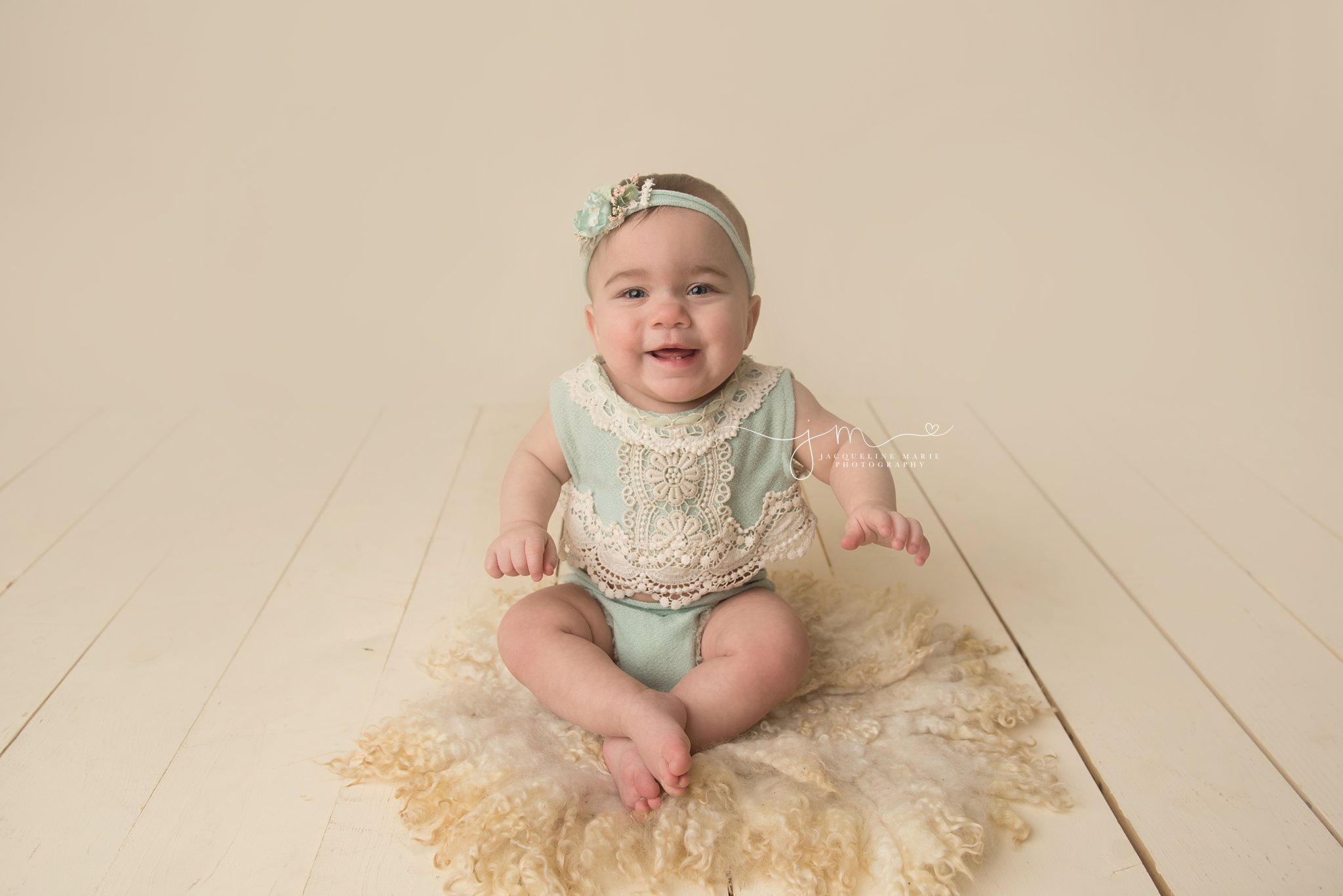 1 year old baby girl wears mint romper and matching headband in columbus ohio portrait studio for first birthday pictures