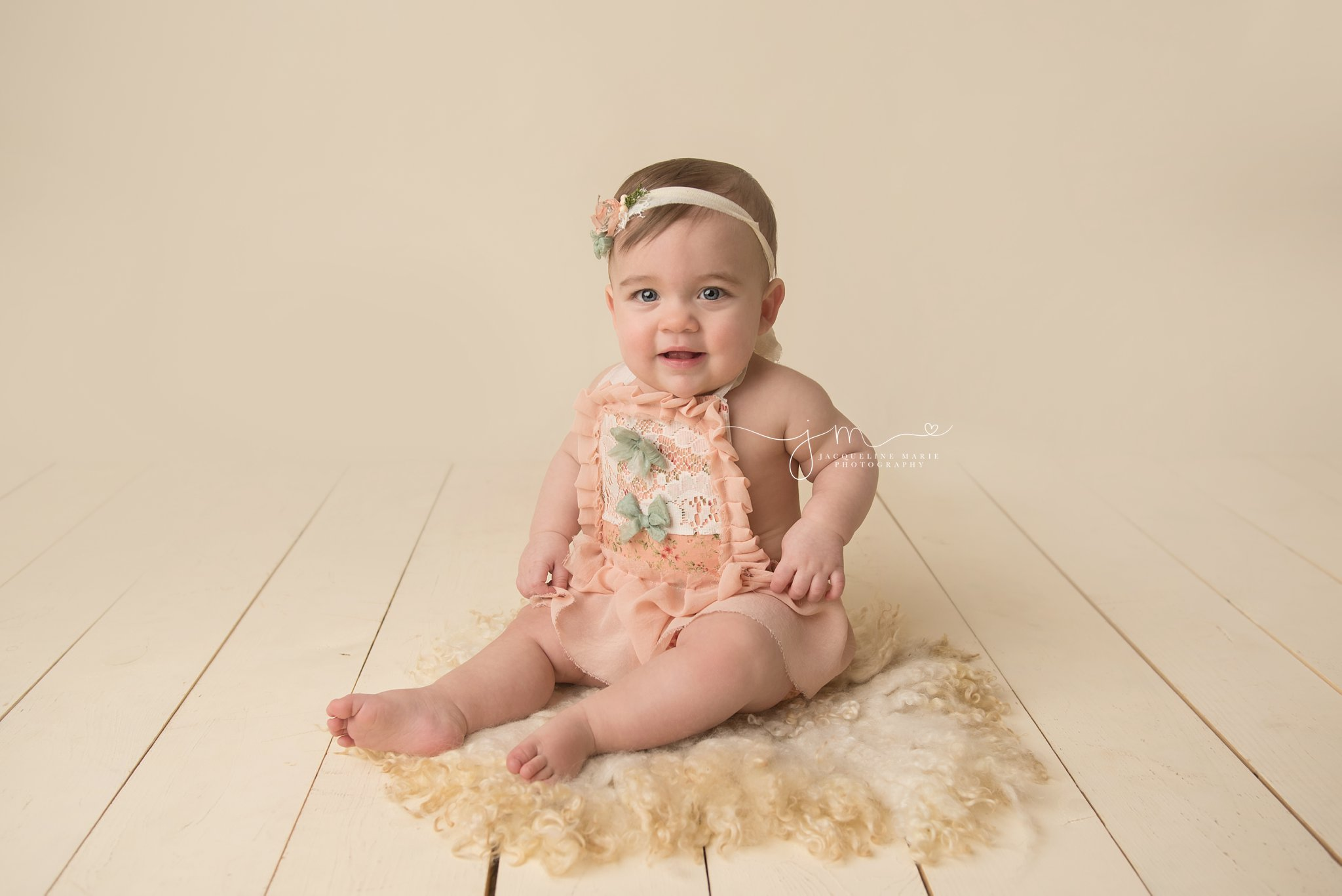 columbus ohio baby photographer poses 1 year old in peach romper and matching headband for first birthday milestone pictures