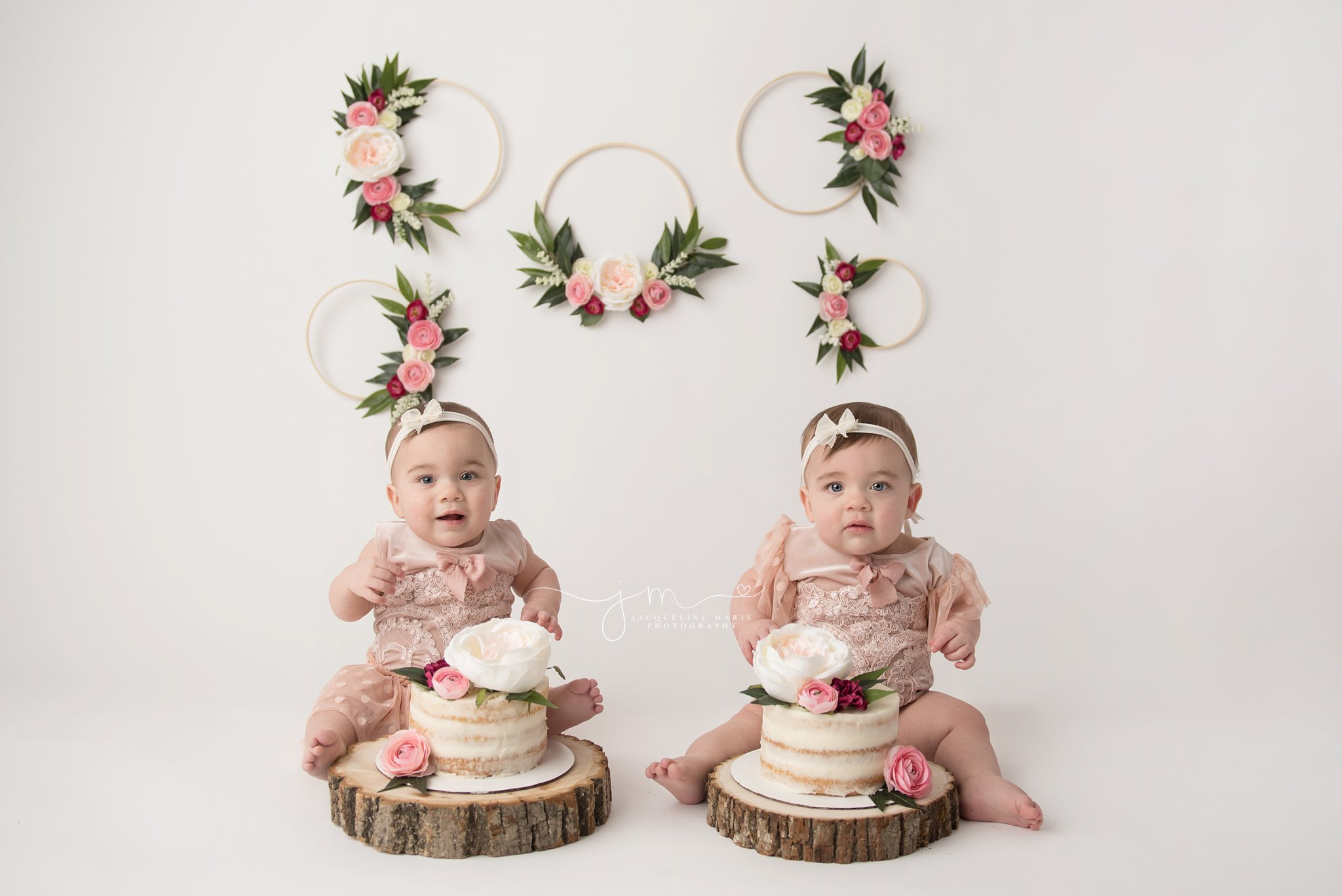 twin sisters wearing matching pink rompers and headbands for floral cake smash pictures in columbus ohio