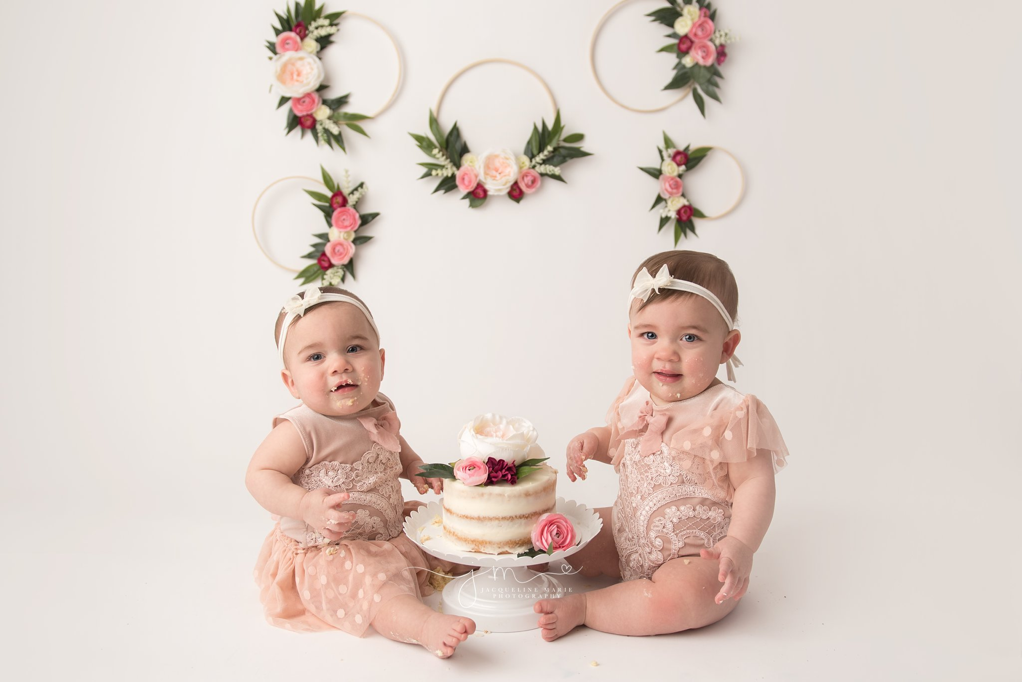 twin sisters share a floral cake for their cake smash pictures in columbus ohio