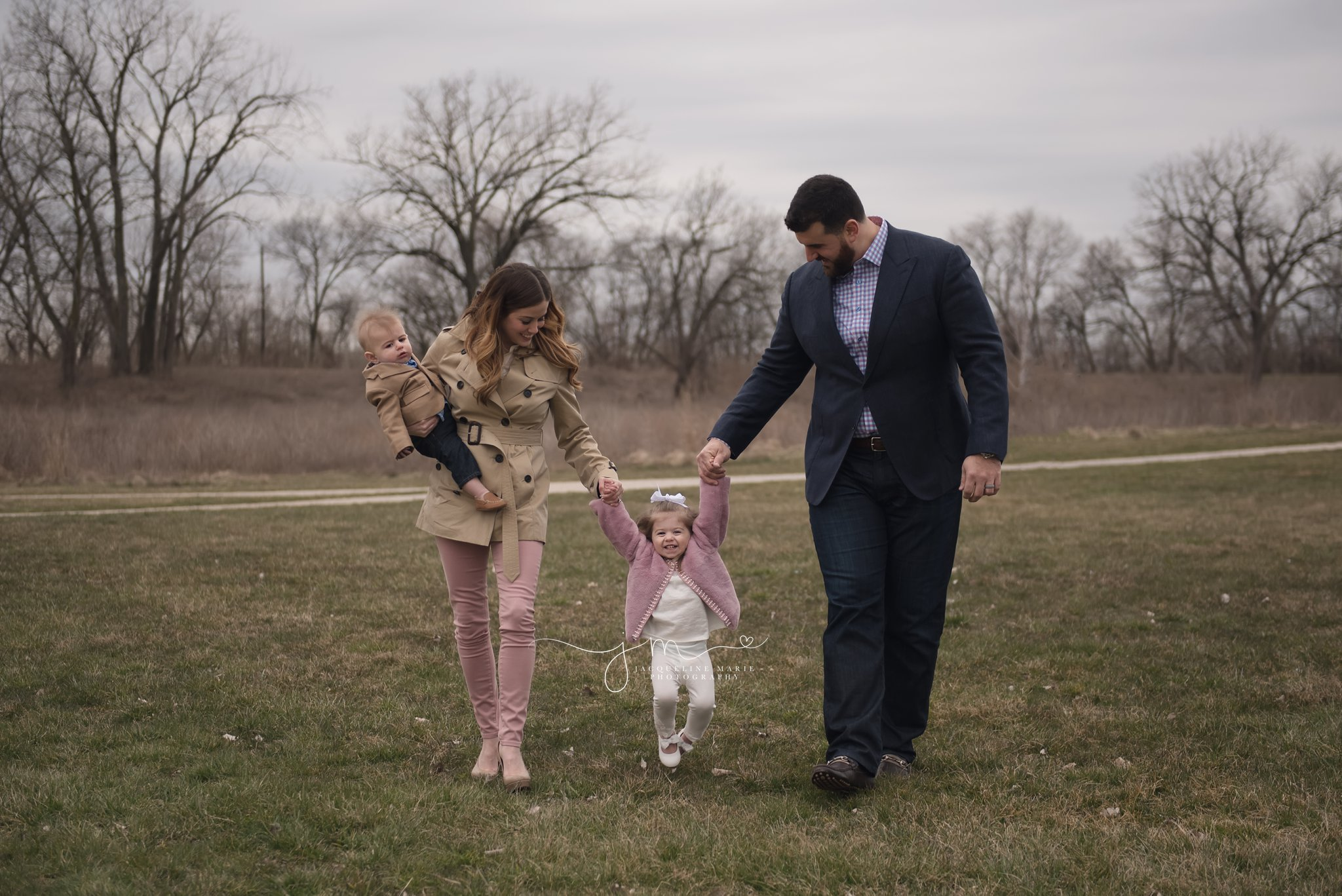 parents walk with baby boy and hold daughter's hand in columbus ohio for family pictures