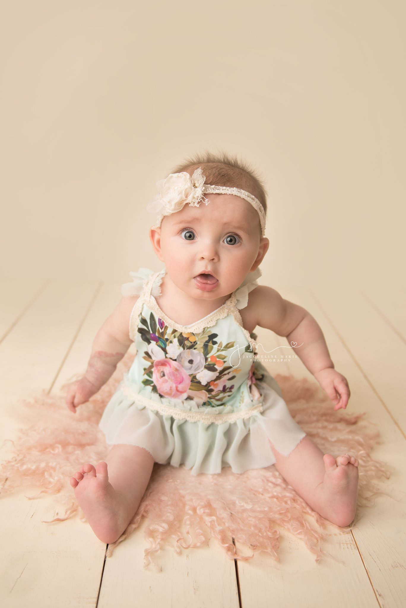 6 month old amelia wears floral romper in columbus ohio for milestone baby portraits