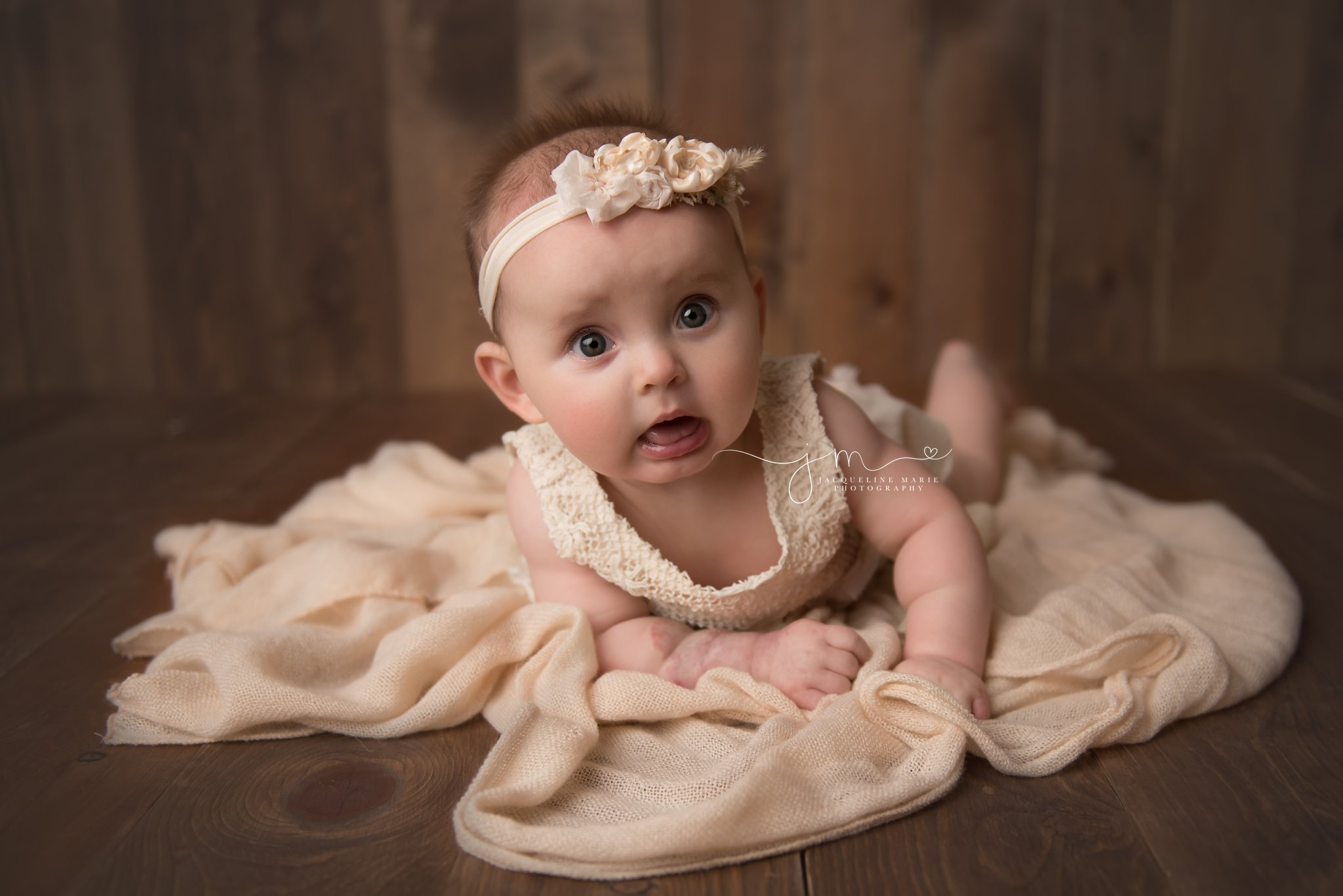 columbus ohio baby girl lays on her belly on blush pink scarf at columbus ohio baby photography studio