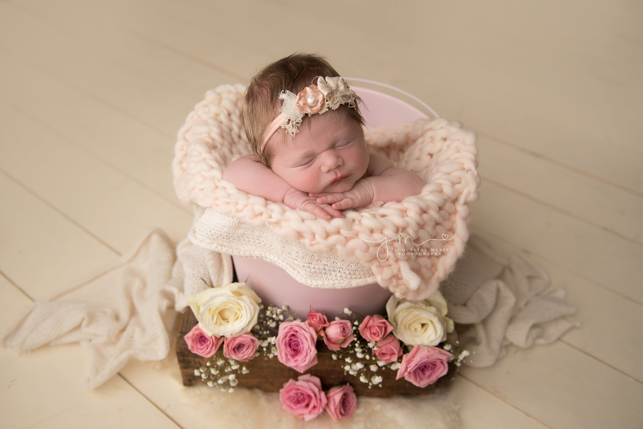1 week old newborn baby girl is sleeping in pink bucket surrounded with pink and cream roses in columbus ohio newborn photography studio