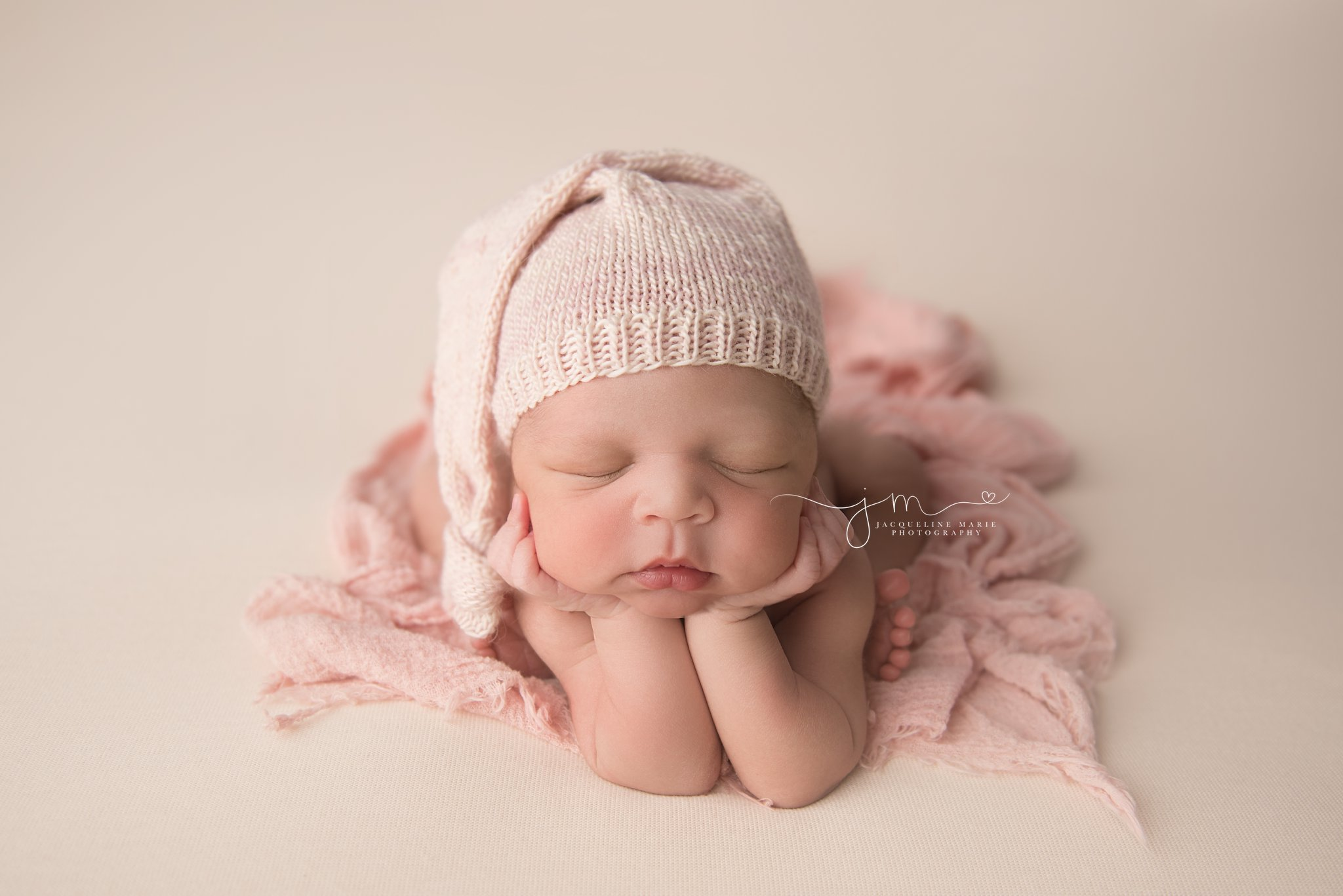 columbus ohio newborn baby girl wears pink sleepy hat for froggy pose during newborn photography session