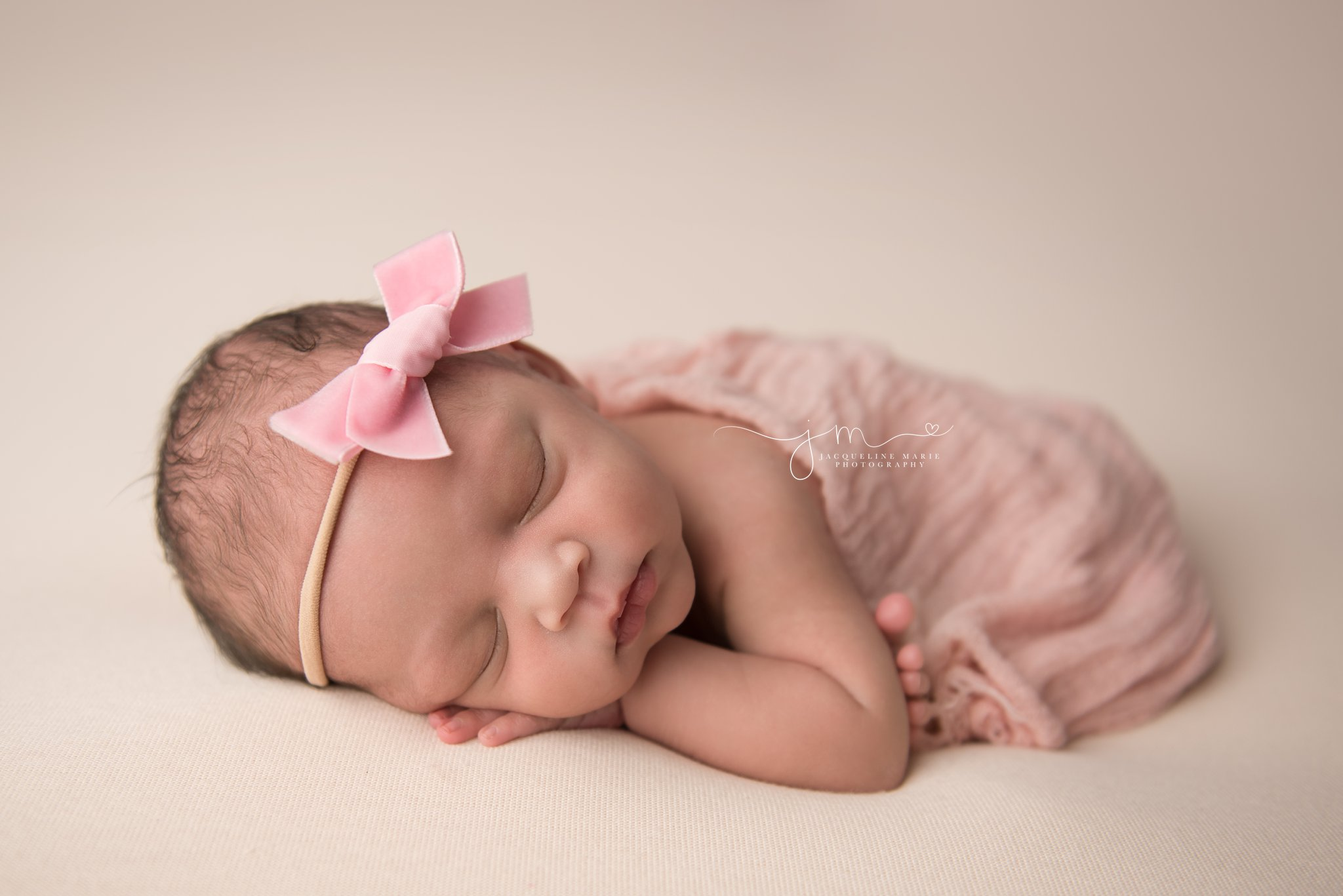 newborn baby girl wears pink bow headband and is wrapped in a matching pink soft wrap at newborn photography studio in columbus ohio