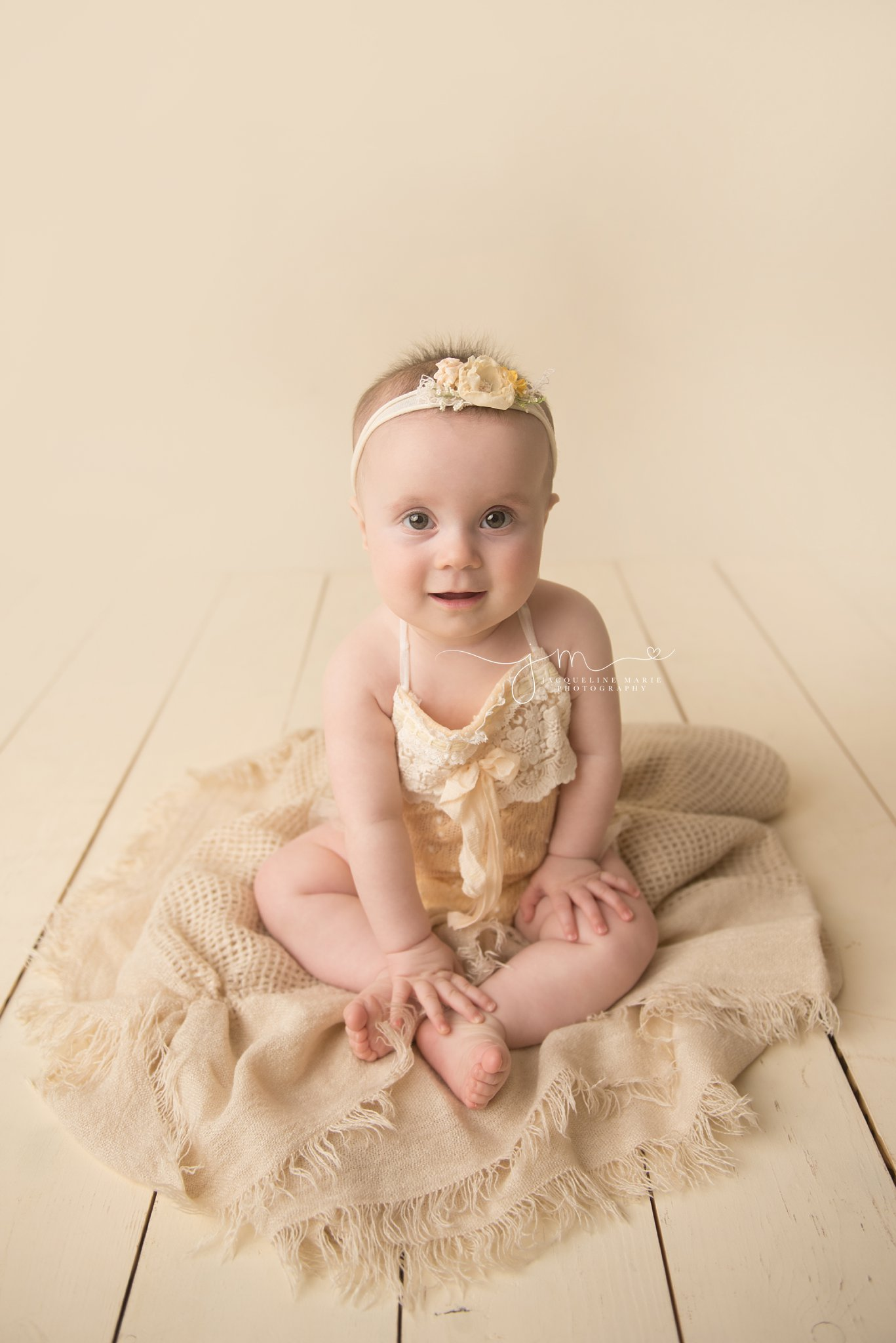 columbus ohio baby girl wears yellow romper while sitting on tan scarf layer at photography studio for 6 month milestone pictures