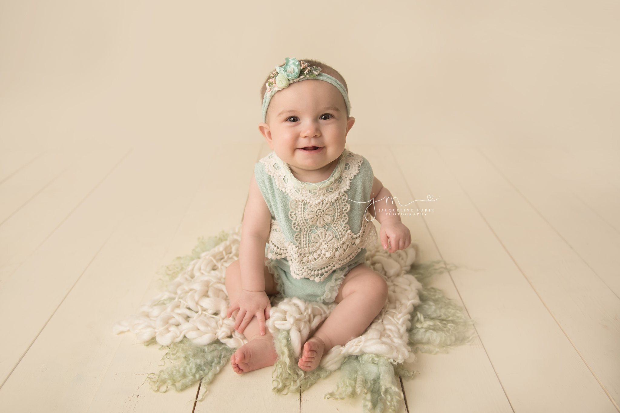 columbus ohio baby photographer poses baby girl in mint green and cream lace romper