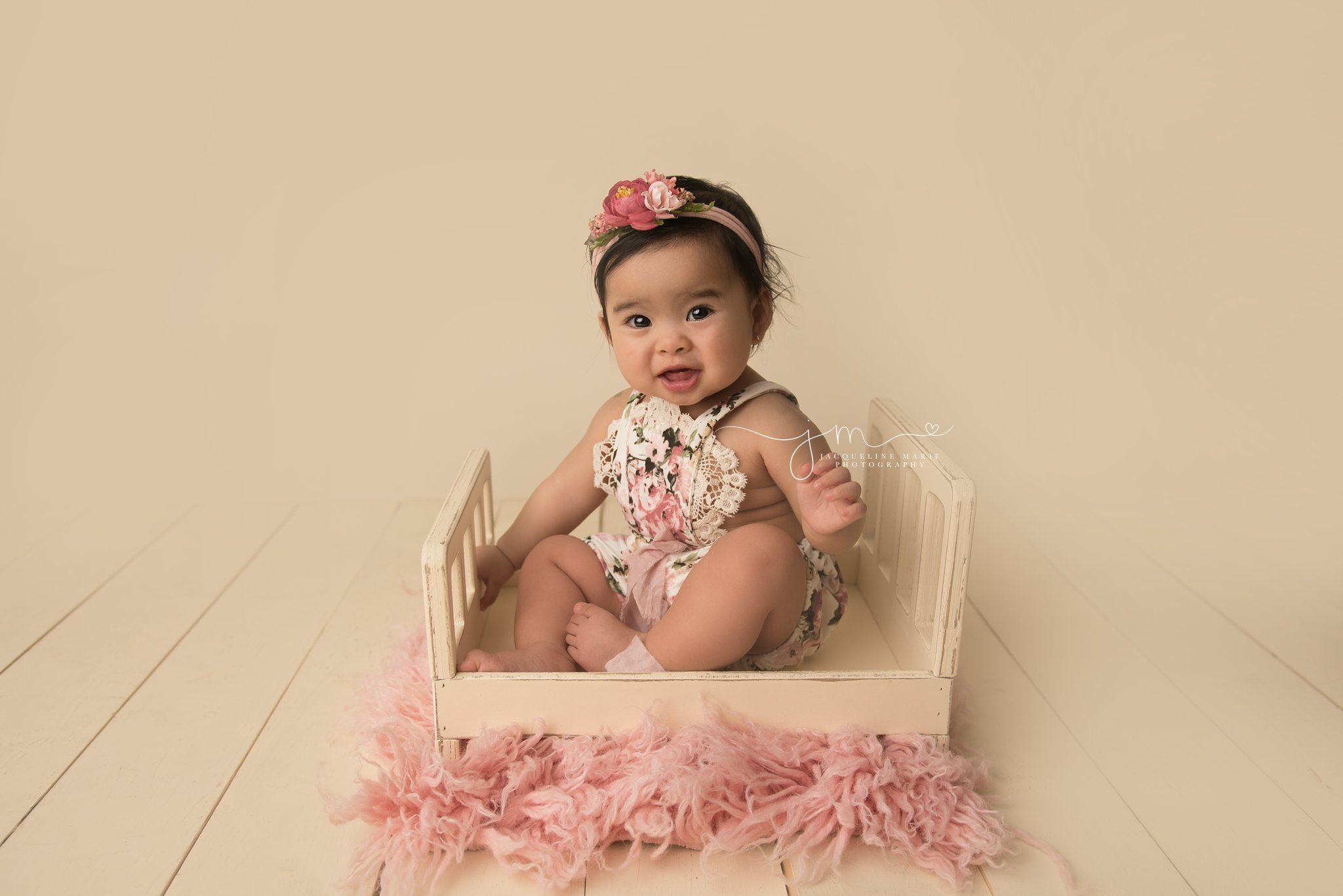 1 year old baby girl wears floral romper while sitting in cream wood bed prop in columbus ohio for first birthday portraits