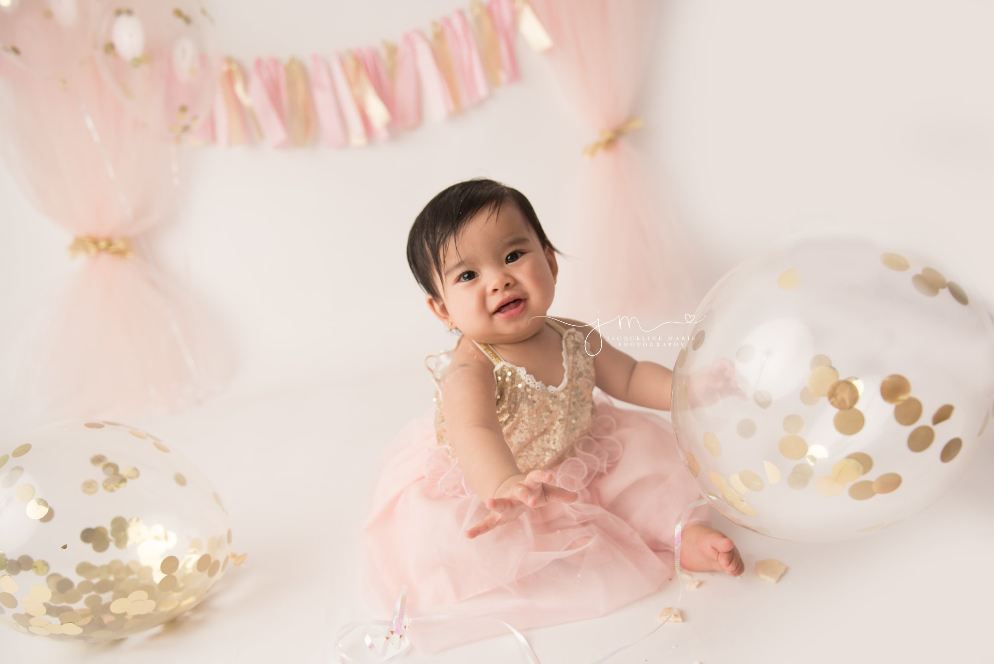 1 year old girl wears gold and pink dress while holding confetti balloon in columbus ohio baby photography studio for cake smash pictures