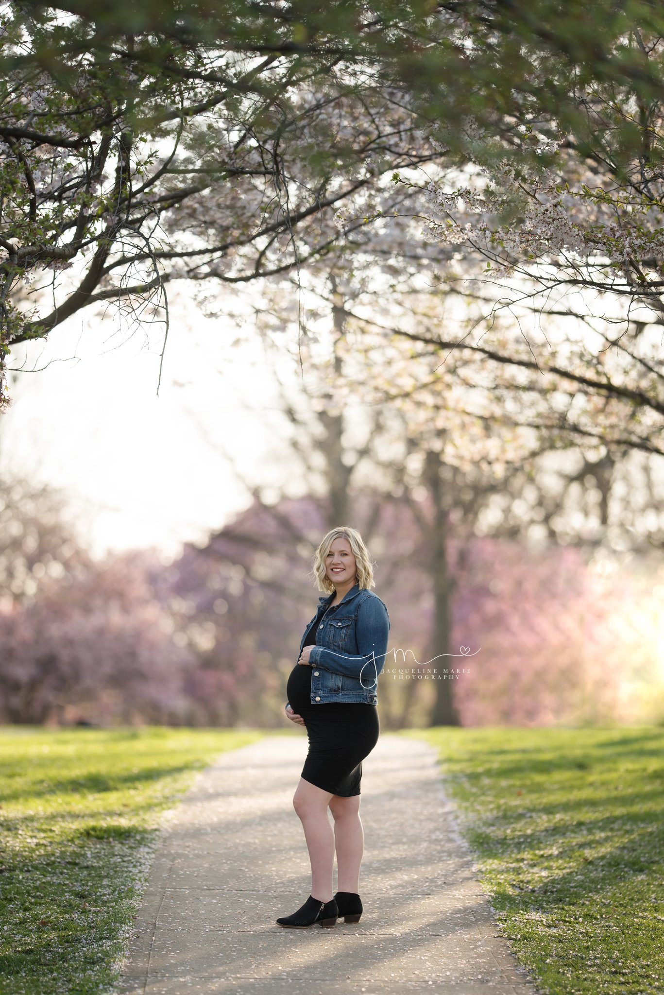 pregnant mother to be stands on sidewalk with beautiful spring bloomed trees in columbus ohio