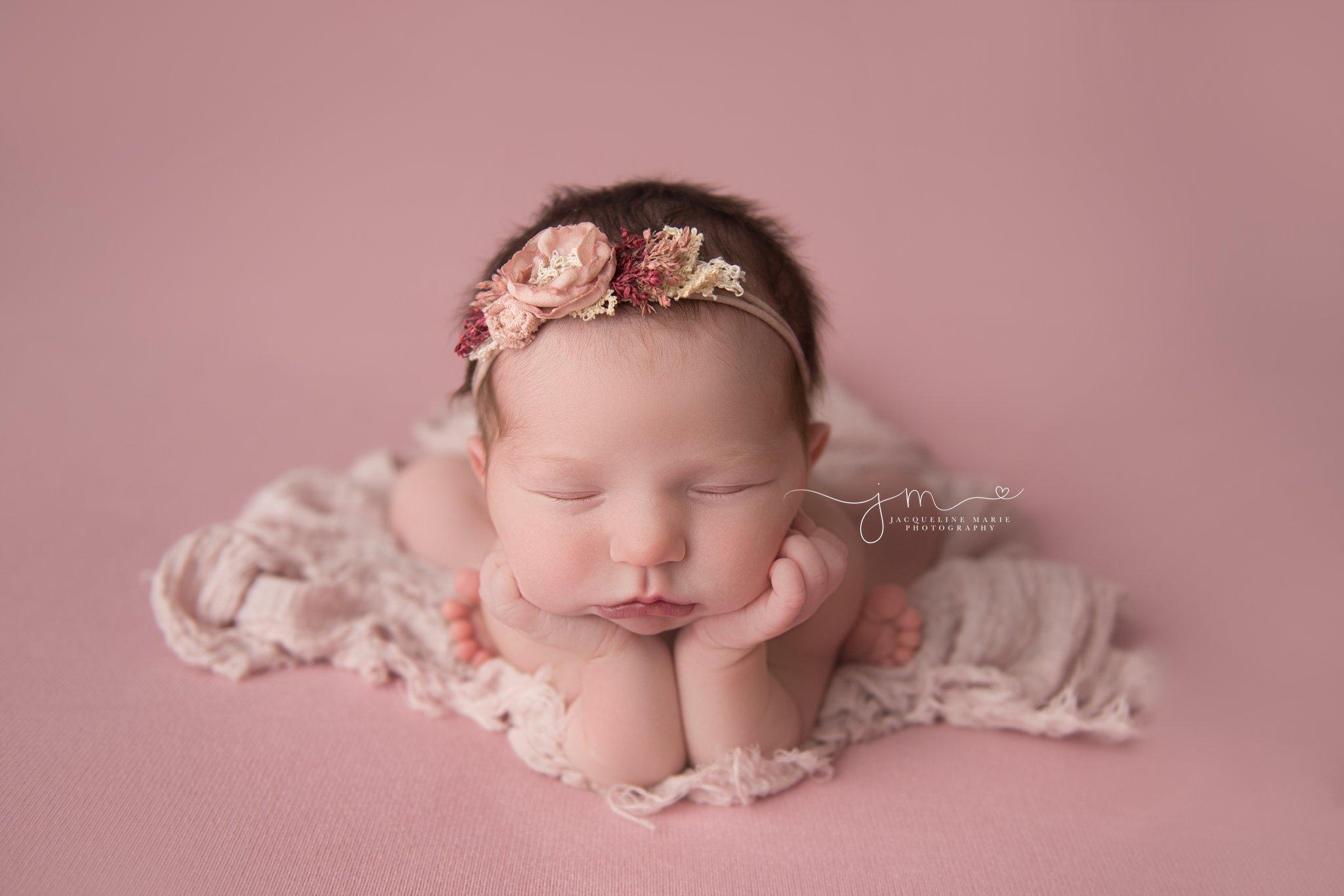 columbus ohio newborn baby girl wears pink floral headband for newborn pictures