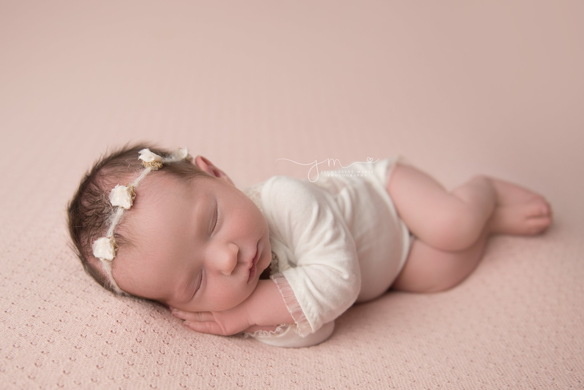 1 week old newborn baby girl wears cream headband and romper while sleeping for newborn photography session