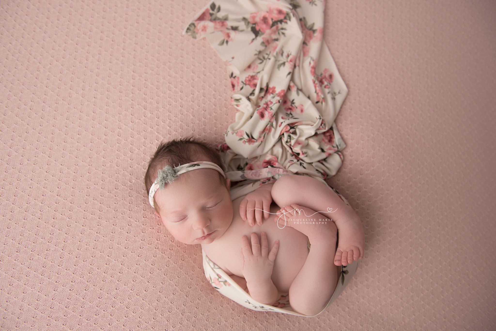 newborn baby girl is wrapped in floral wrap for newborn pictures in columbus ohio