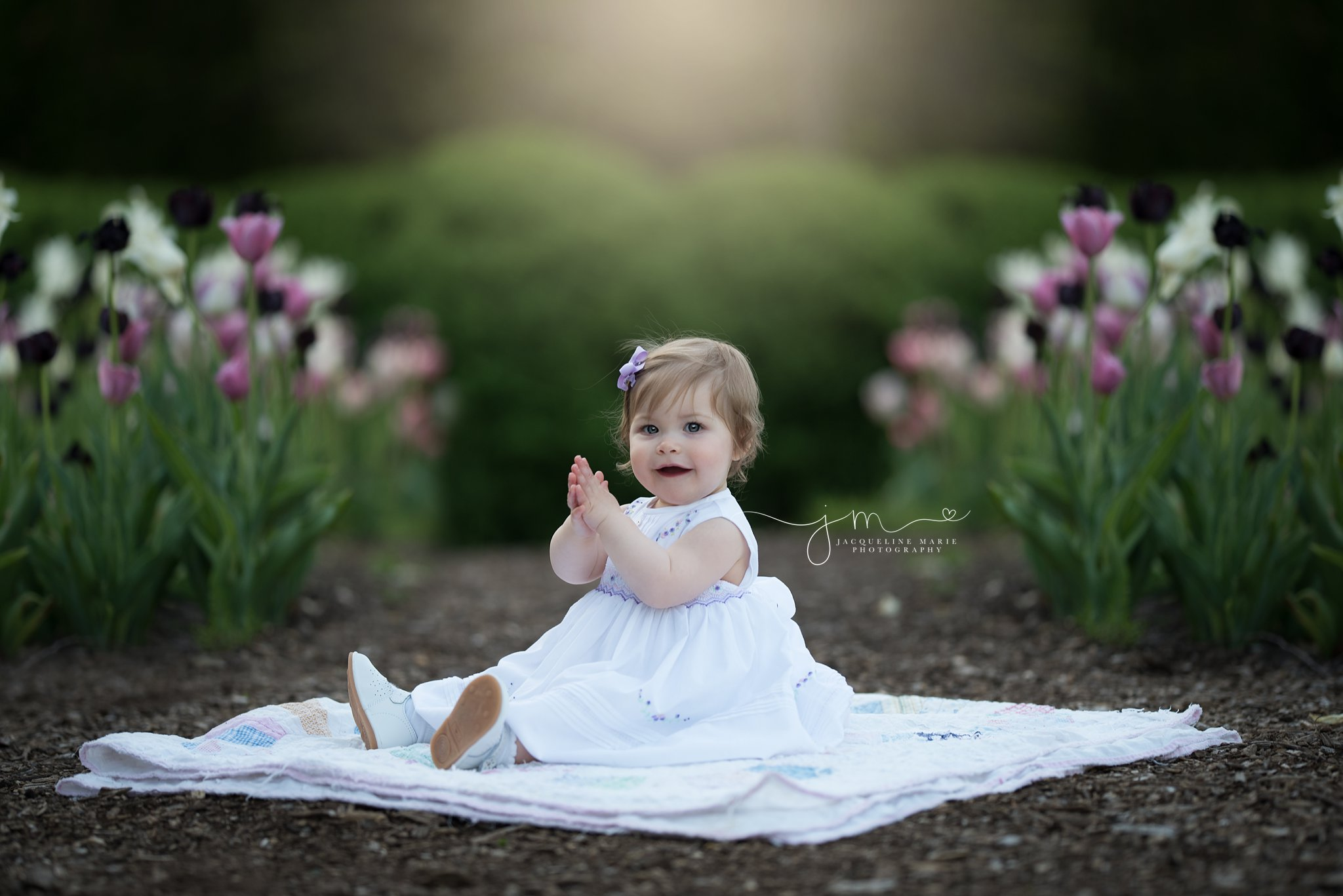 1 year old baby girl wears white dress while sitting with tulips in columbus ohio