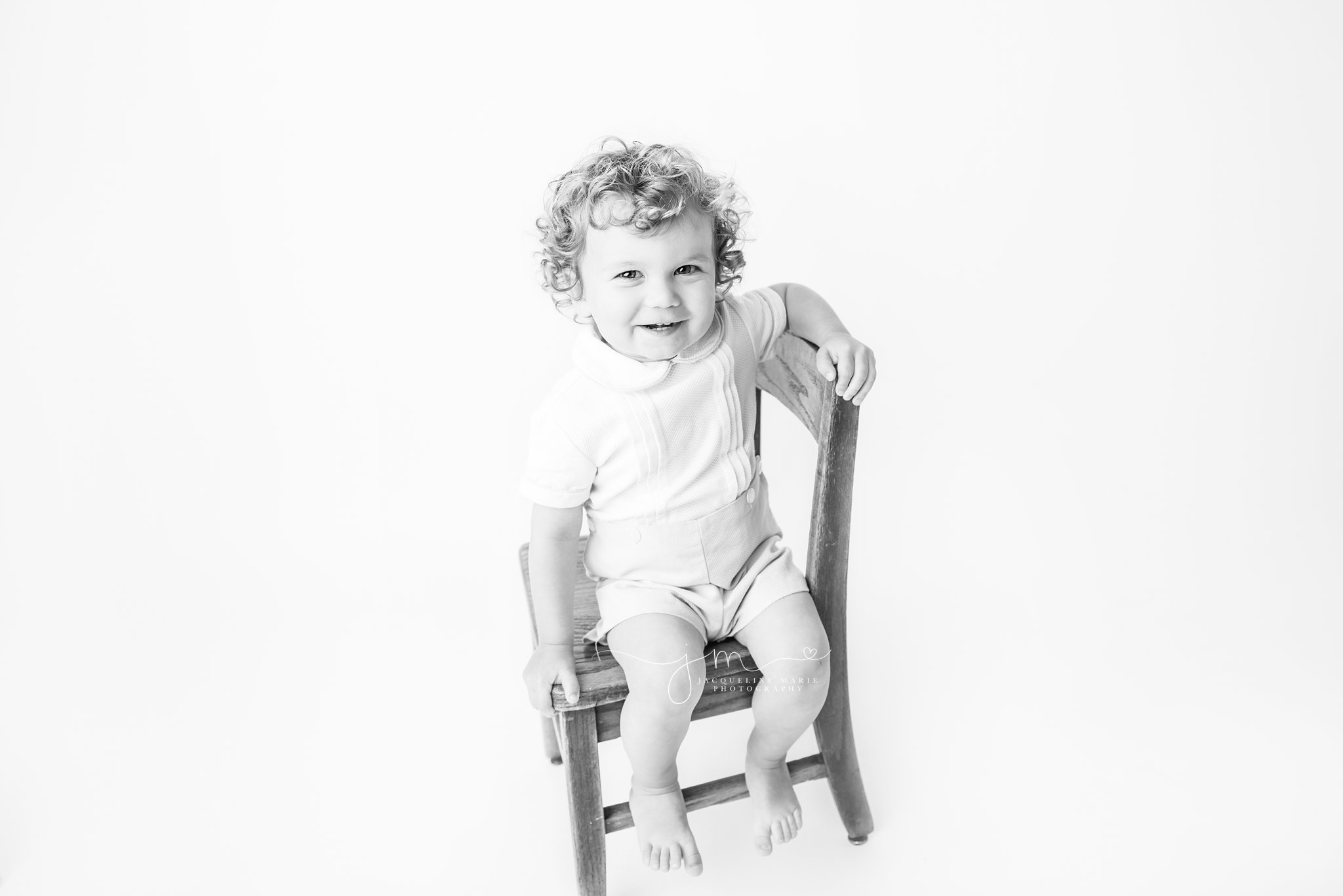2 year old sits on wood chair for milestone black and white session in columbus ohio photography studio