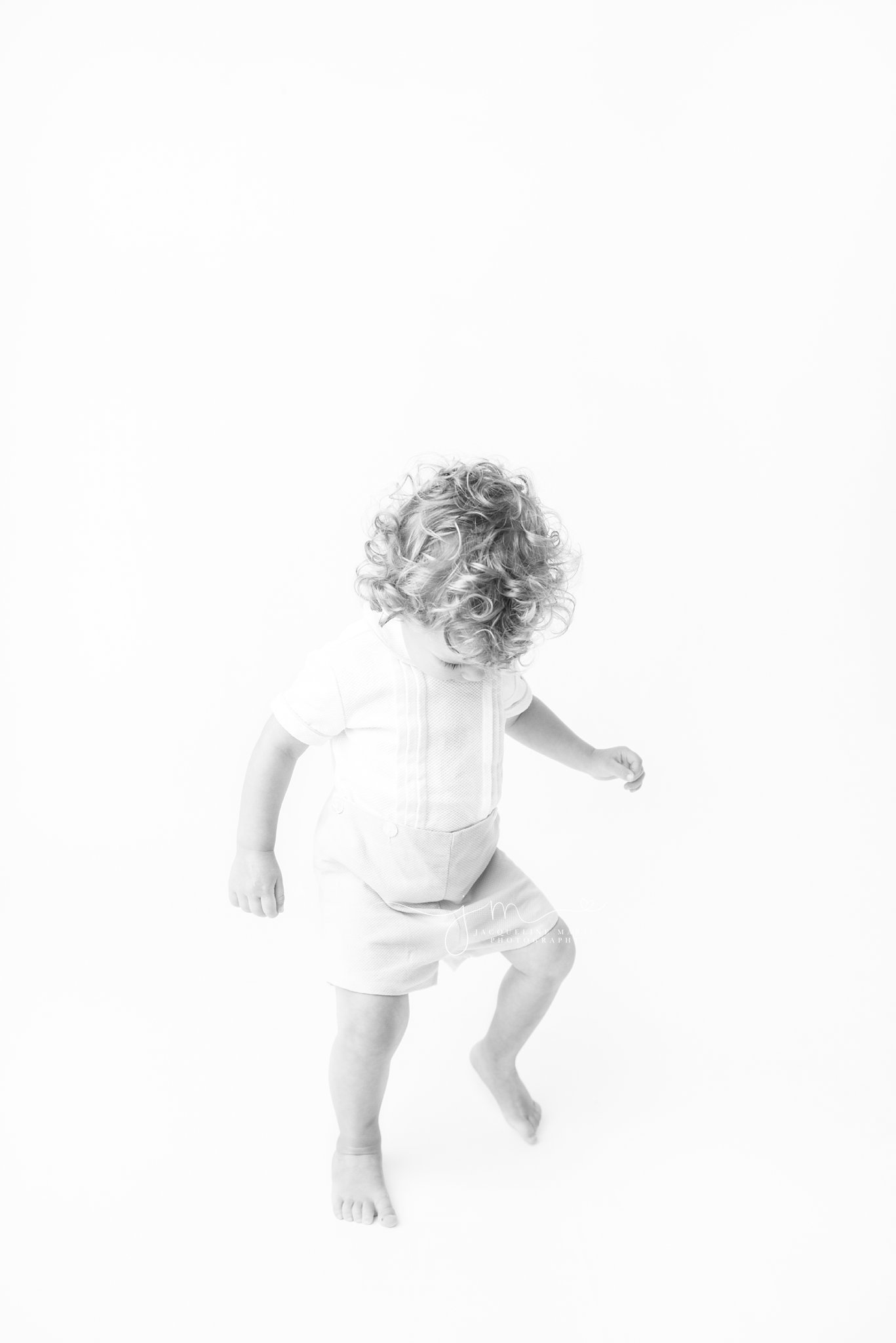 little boy is walking in a vintage romper during milestone photo session in columbus ohio