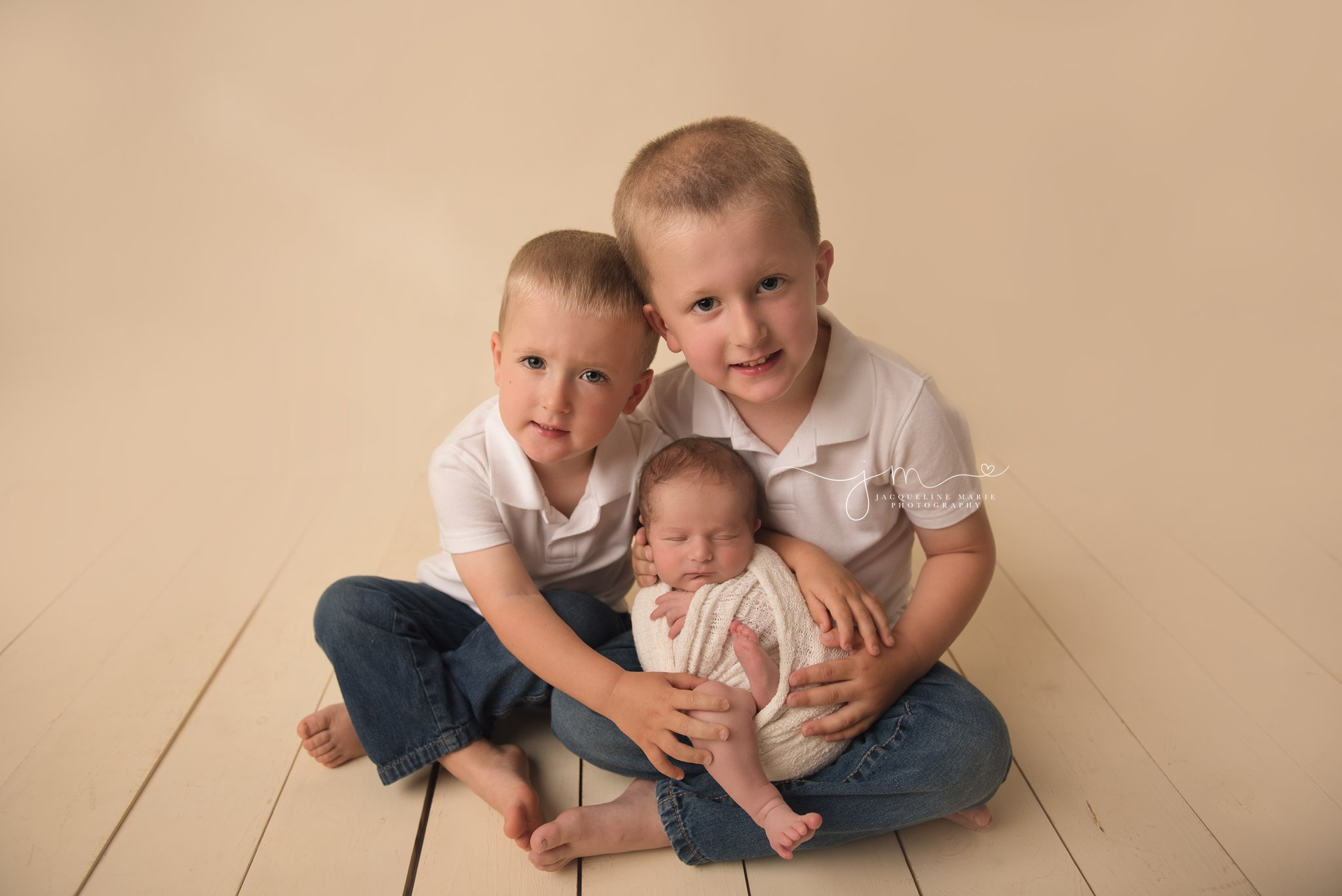 older siblings hold younger brother for newborn photography in colymbus ohio