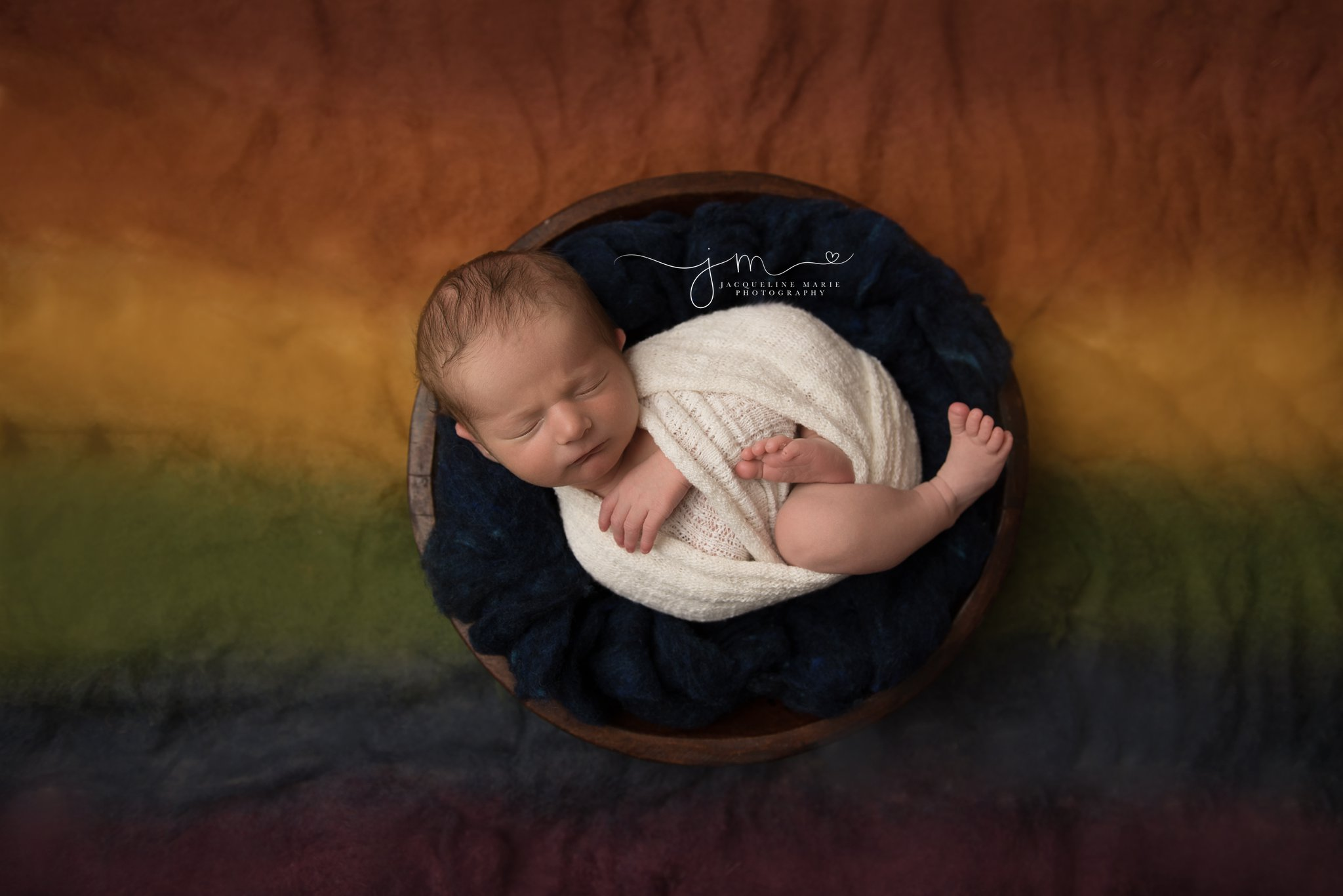 rainbow baby boy swaddled in cream wrap and rainbow blanket in columbus ohio newborn photography studio