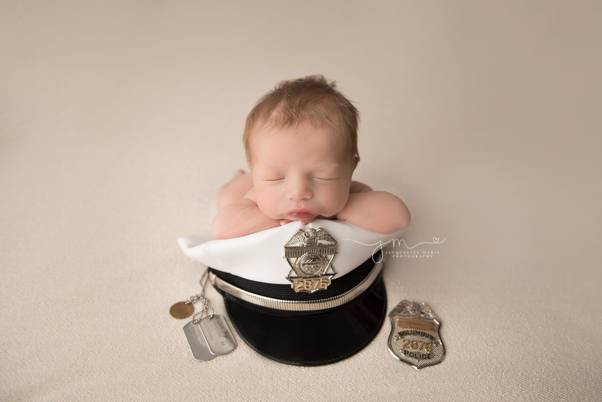 columbus ohio newborn bay boy is posed with his daddy's police hat and badge for newborn portraits