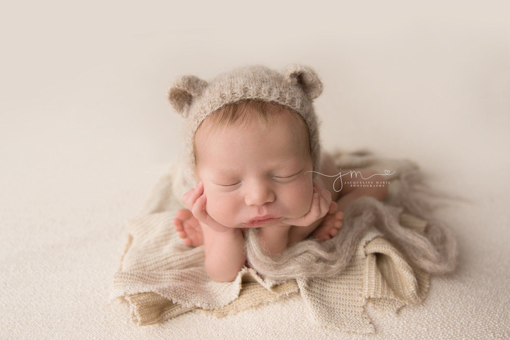 newborn baby boy wears teddy bear bonnet for froggy pose in columbus ohio