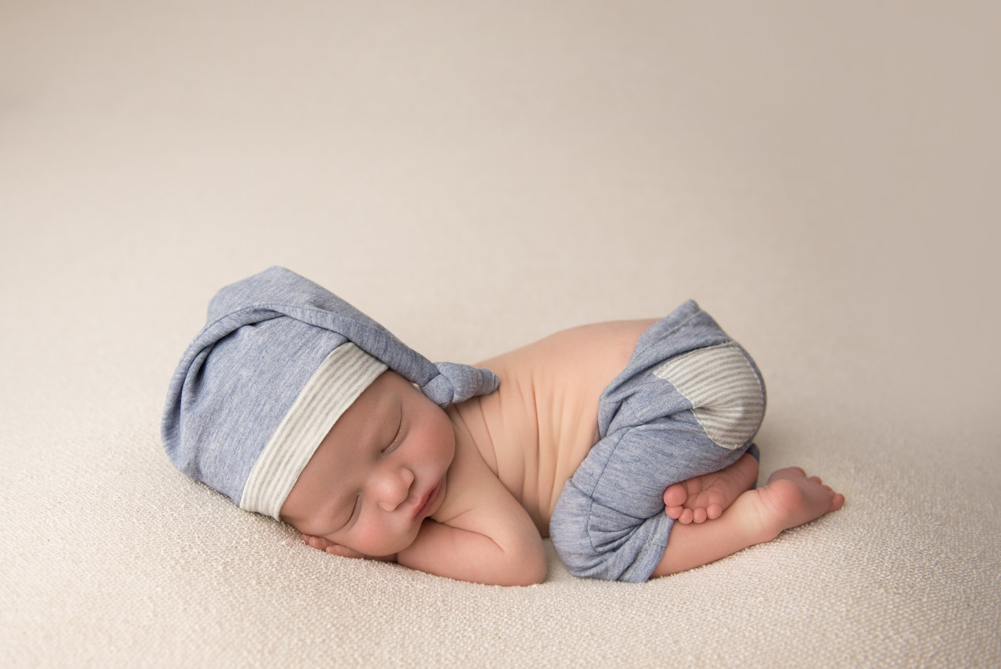 columbus ohio newborn photographer poses baby boy in blue and gray pants and hat set for newborn photography session