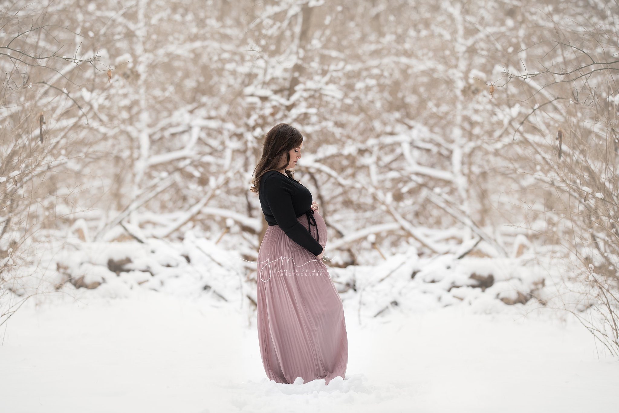 winter maternity session in the snow wearing pink dress