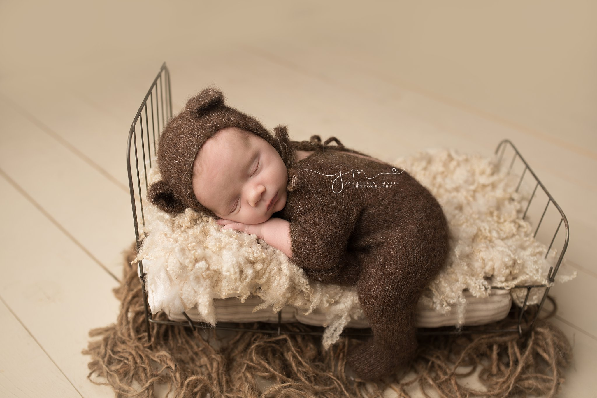 newborn baby wears teddy bear bonnet for newborn photography session in columbus ohio