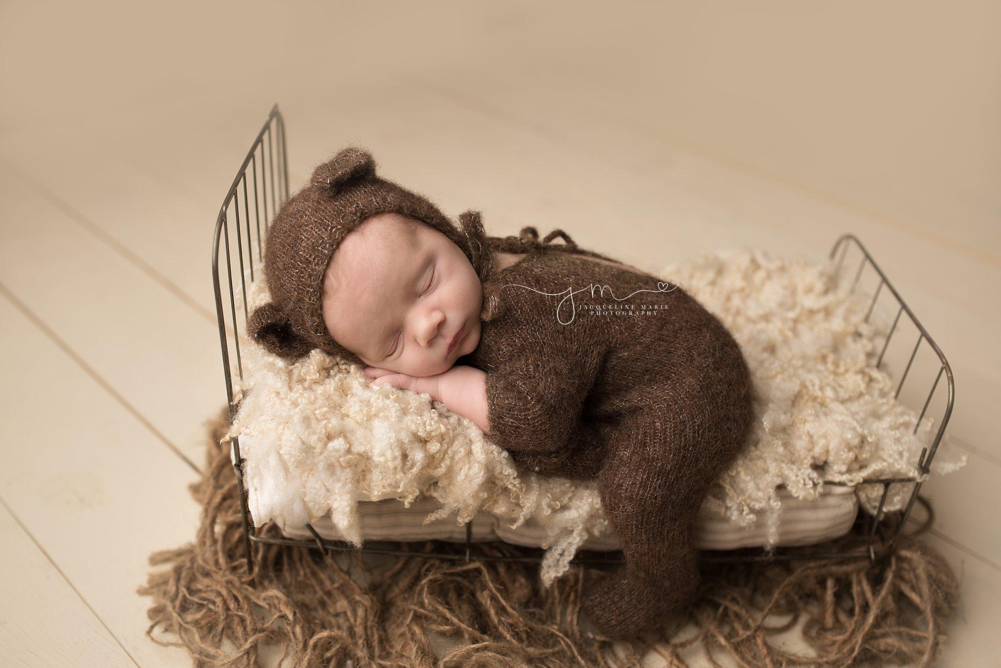newborn baby wears teddy bear bonnet for newborn photography session in columbus ohio