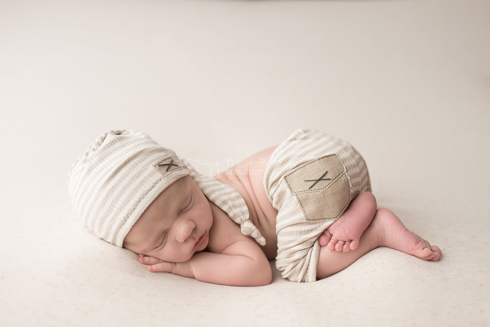 columbus ohio newborn photographer poses baby in neutral hat and pants for newborn portraits
