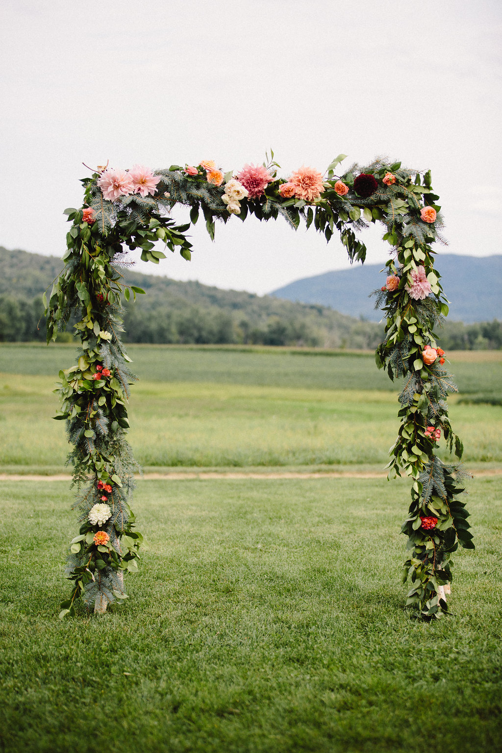 Ceremony flower arrangements by Nectar & Root | Wedding floral design services in Burlington, Vermont (VT) | Arch with coral dahlias, blush garden roses, spray roses