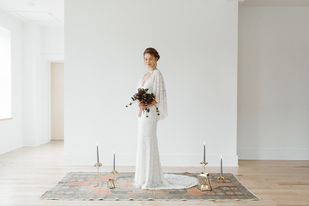 Ceremony flower arrangements by Nectar & Root | Wedding floral design services in Burlington, Vermont (VT) | Moder altar vows area with bohemian rug, anthropologie lanterns, anthro tapered candleholders
