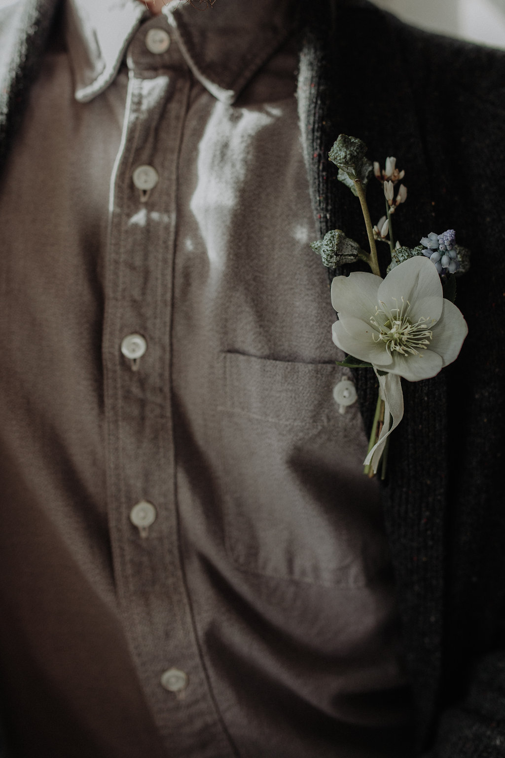 Winter wedding flowers by Nectar & Root | Wedding floral design services in Burlington, Vermont (VT) | Boutonniere with hellebore, eucalyptus pod, grape hyacinth, muscari