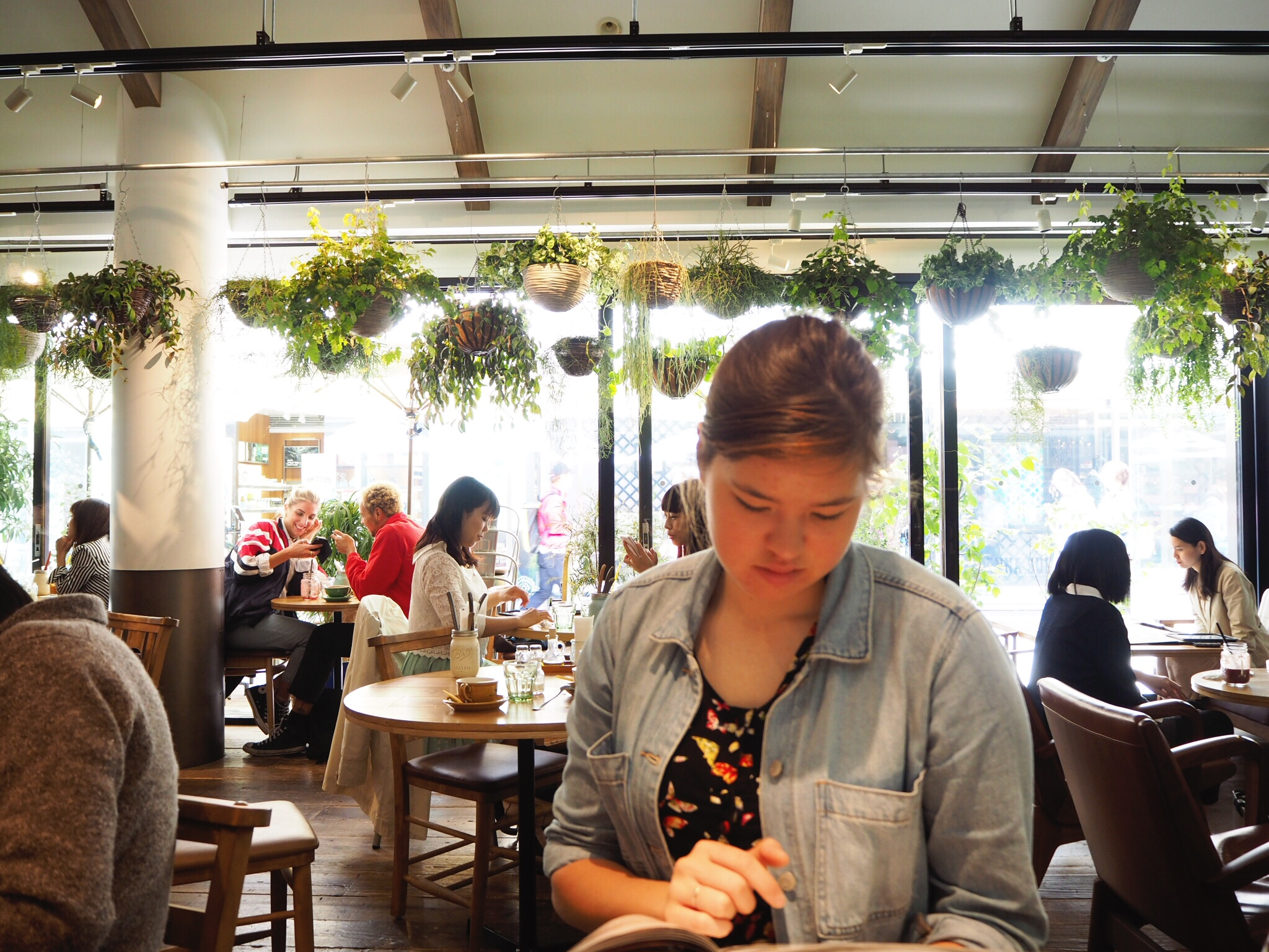 Sister checking out the menu in Hello Farmer, a plant-filled cafe in Shinjuku.