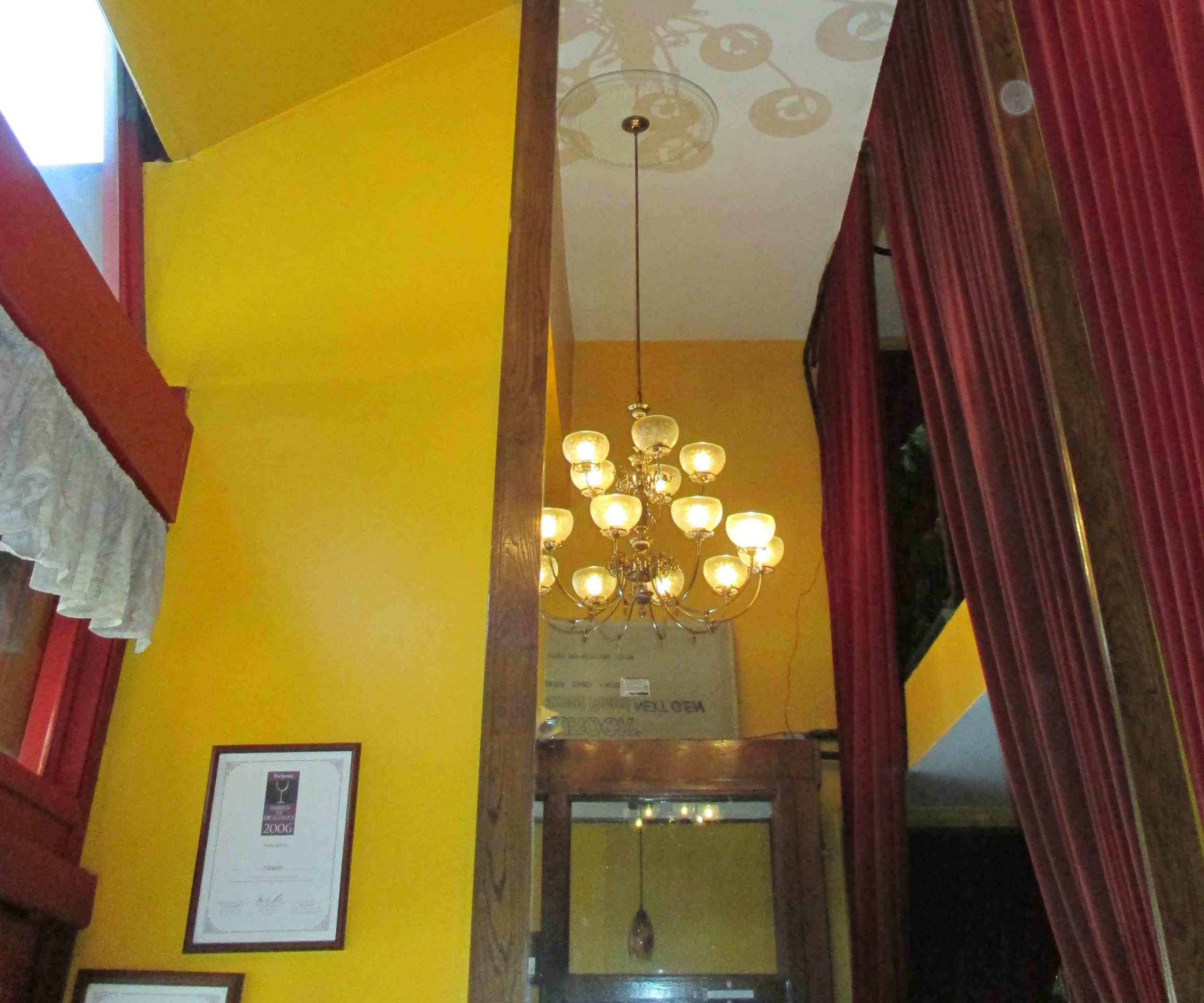 BEFORE: The double height entry space featured bright yellow walls and burgundy curtains.