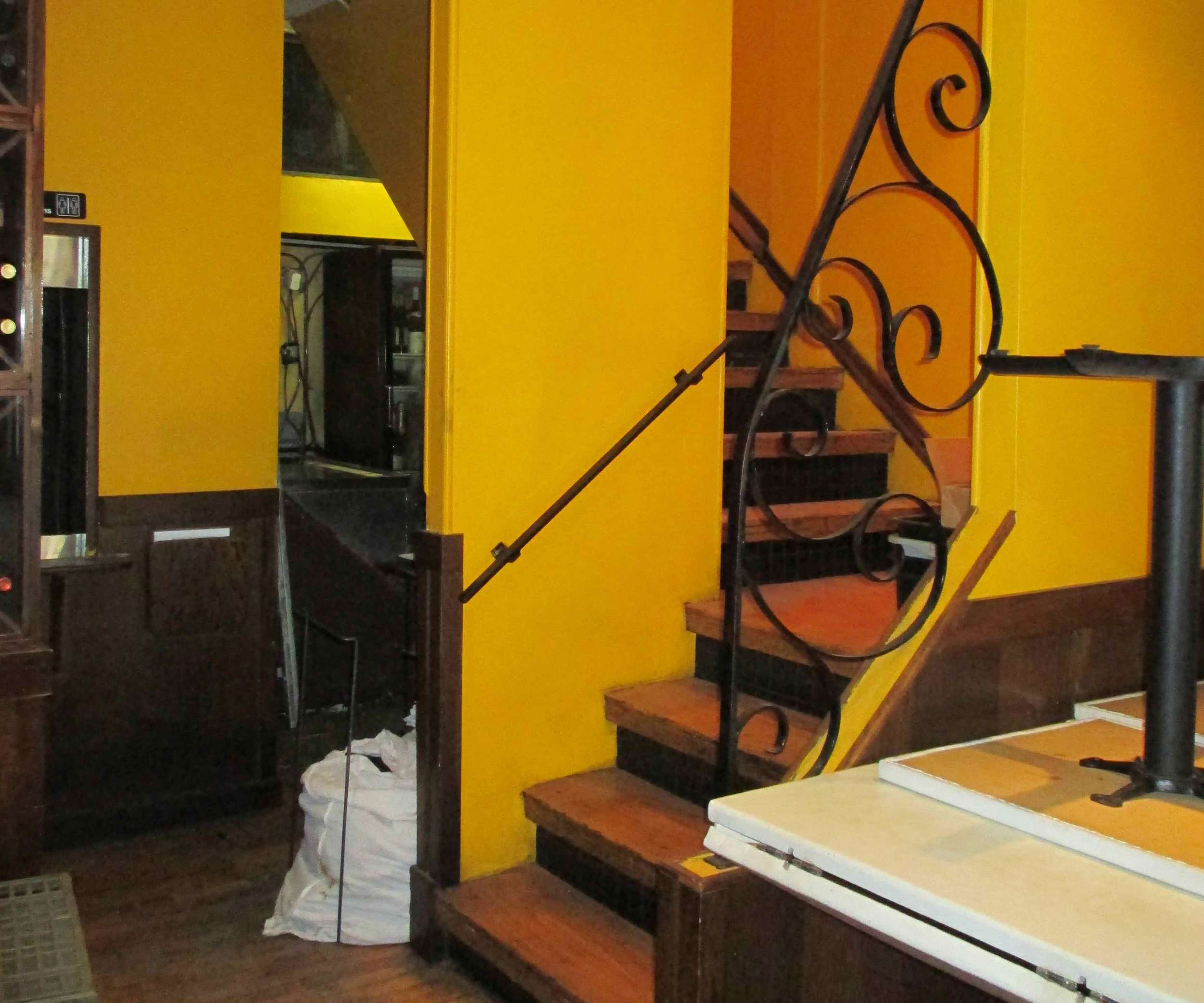 BEFORE: A swirly handrail defines the staircase area.