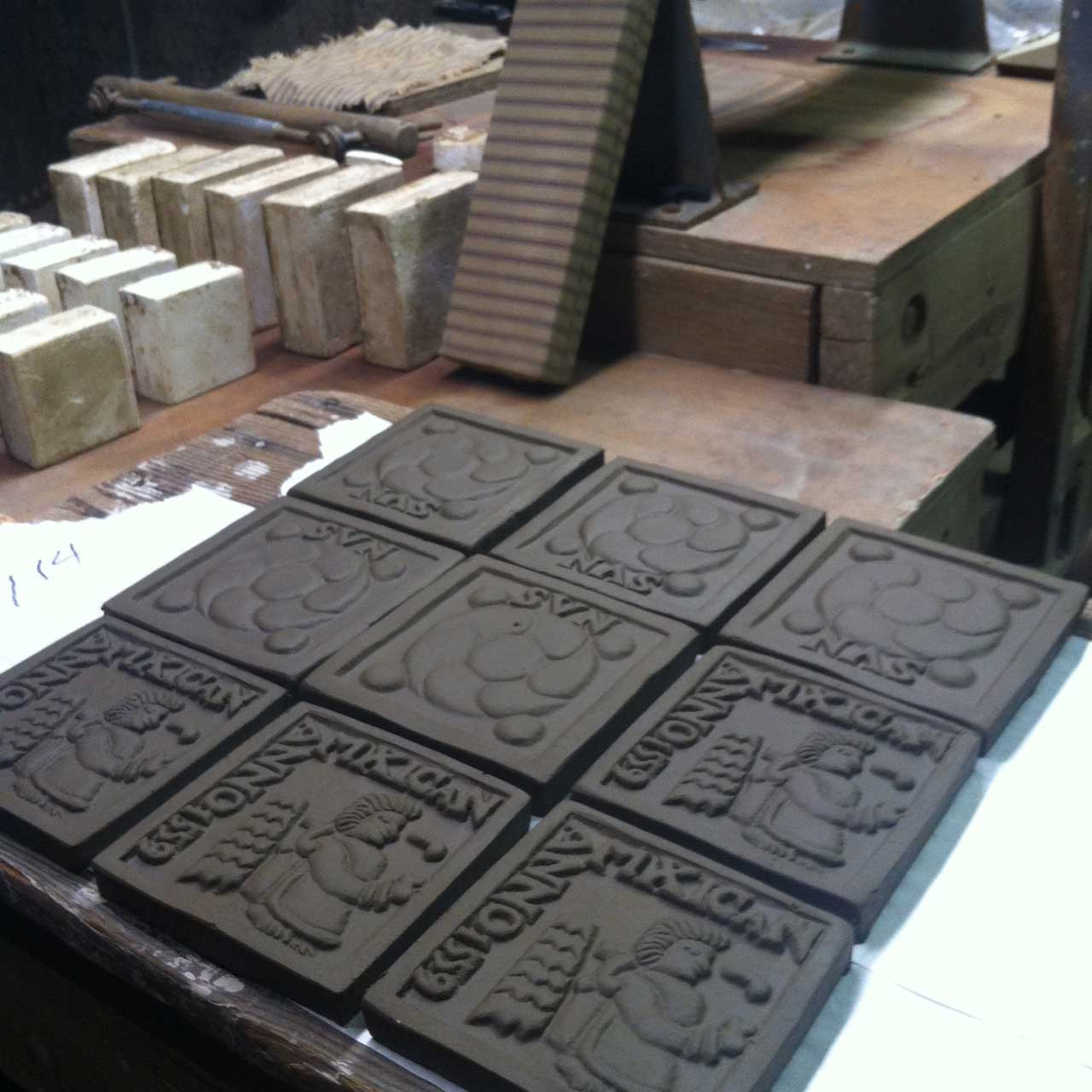 These tiles have just been stamped, and will dry for several weeks before they are glazed and fired.