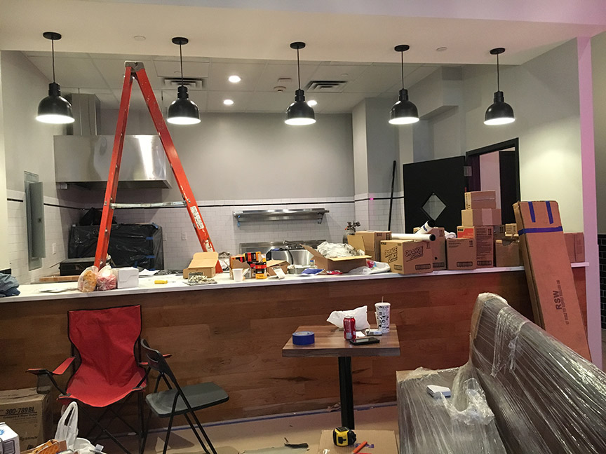 The back kitchen area is totally transformed. Bye bye to those garish colors. The new kitchen is clean and sleek with classic white subway tile, stainless steel shelving, and soft grey walls. The new counter and pendant lights are in place, and they look great.