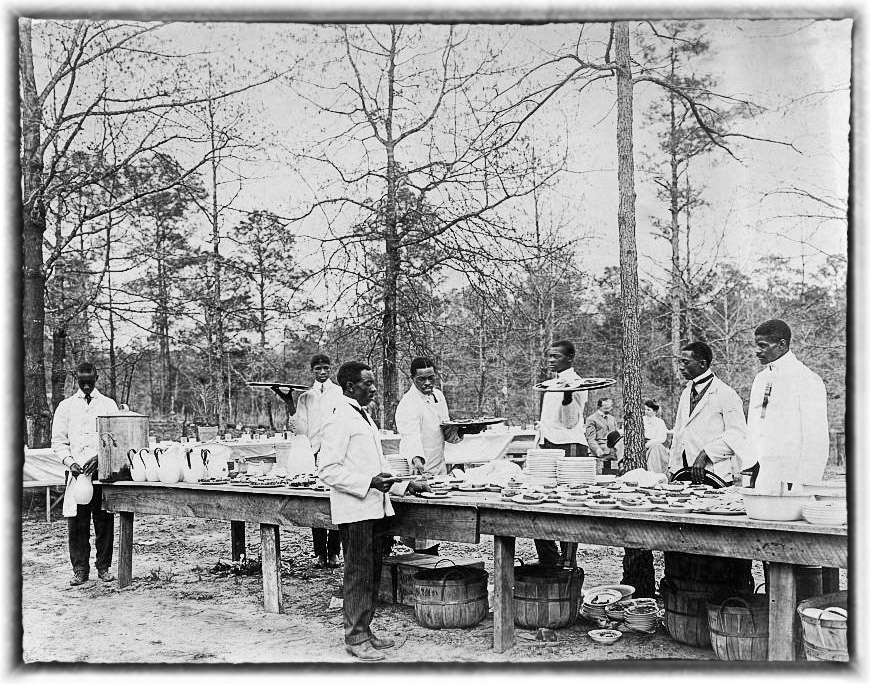 African American men preparing to serve a meal in an outdoor setting among trees at Tuskegee Institu.jpg