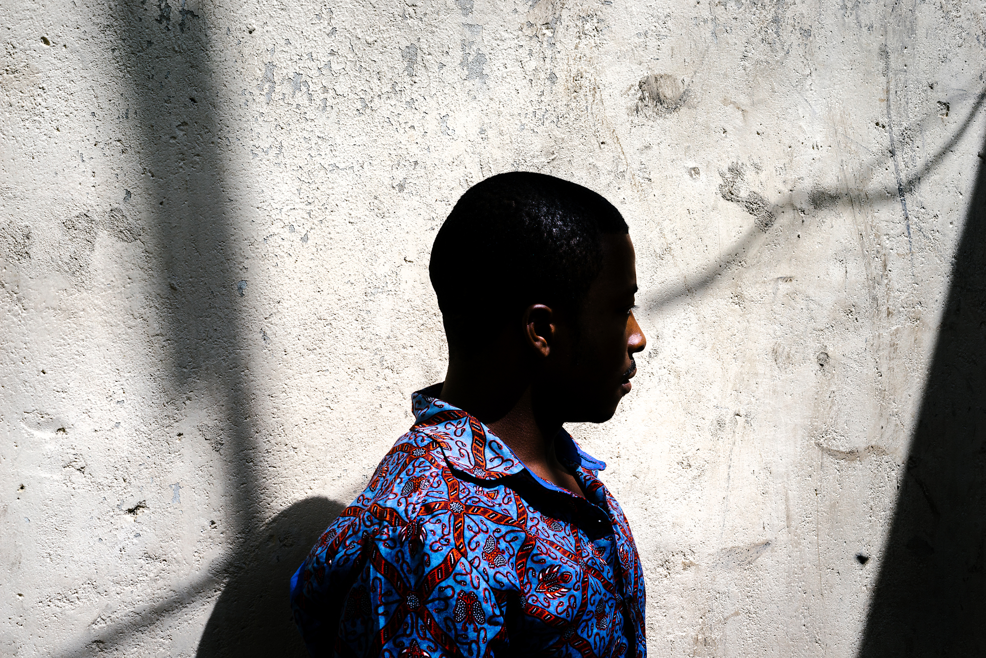 A gay refugee poses for a portrait in front of his home in Nairobi. He was kicked out of his previous apartment by his landlord and beaten by a band of thugs. Now, he lives in hiding.