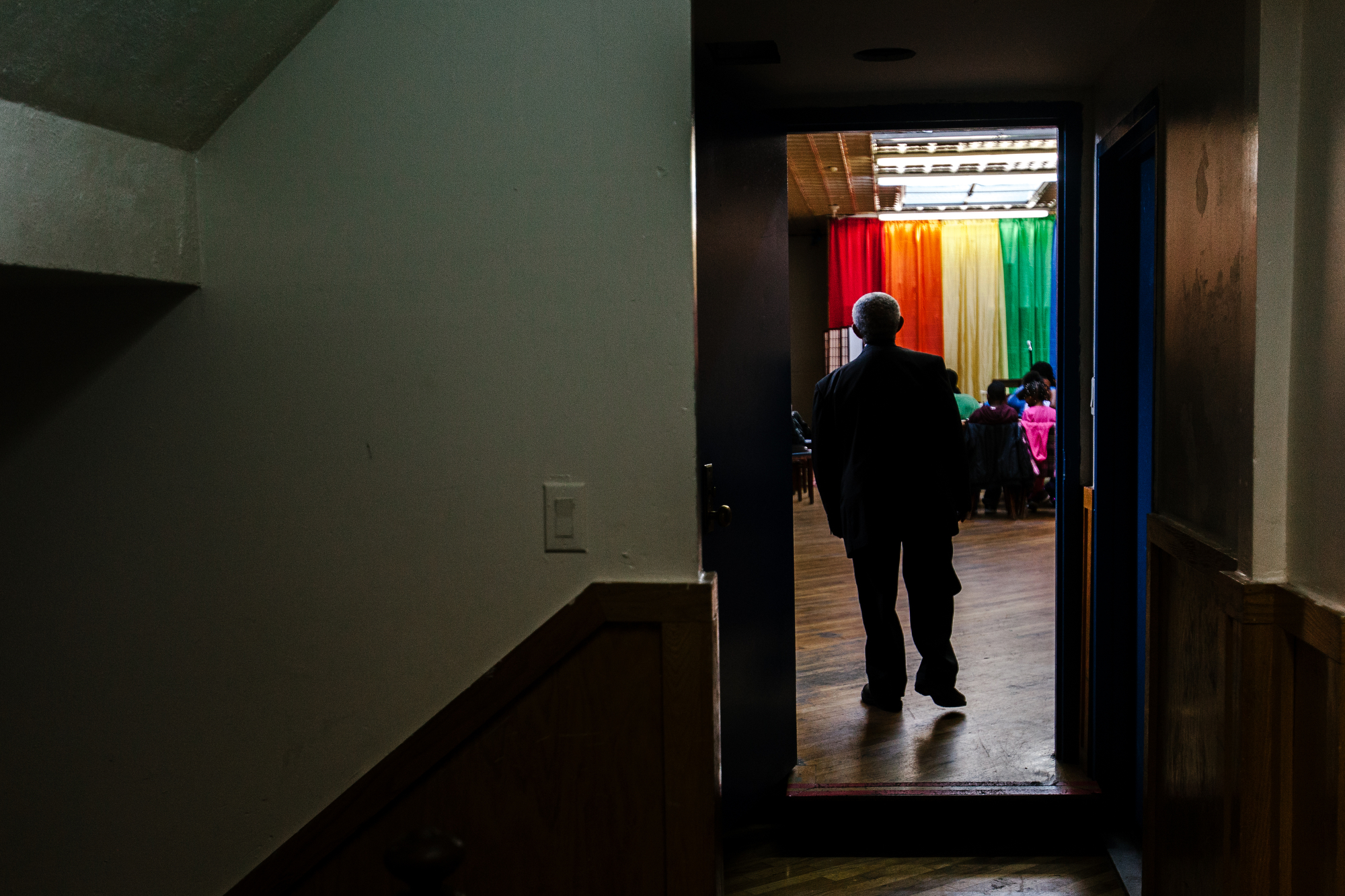 Ernestine, one of the church's longstanding members and its head usher, walks into the church space before service. The space is rented by the week and has no permanent space, though it has been in this location for years.