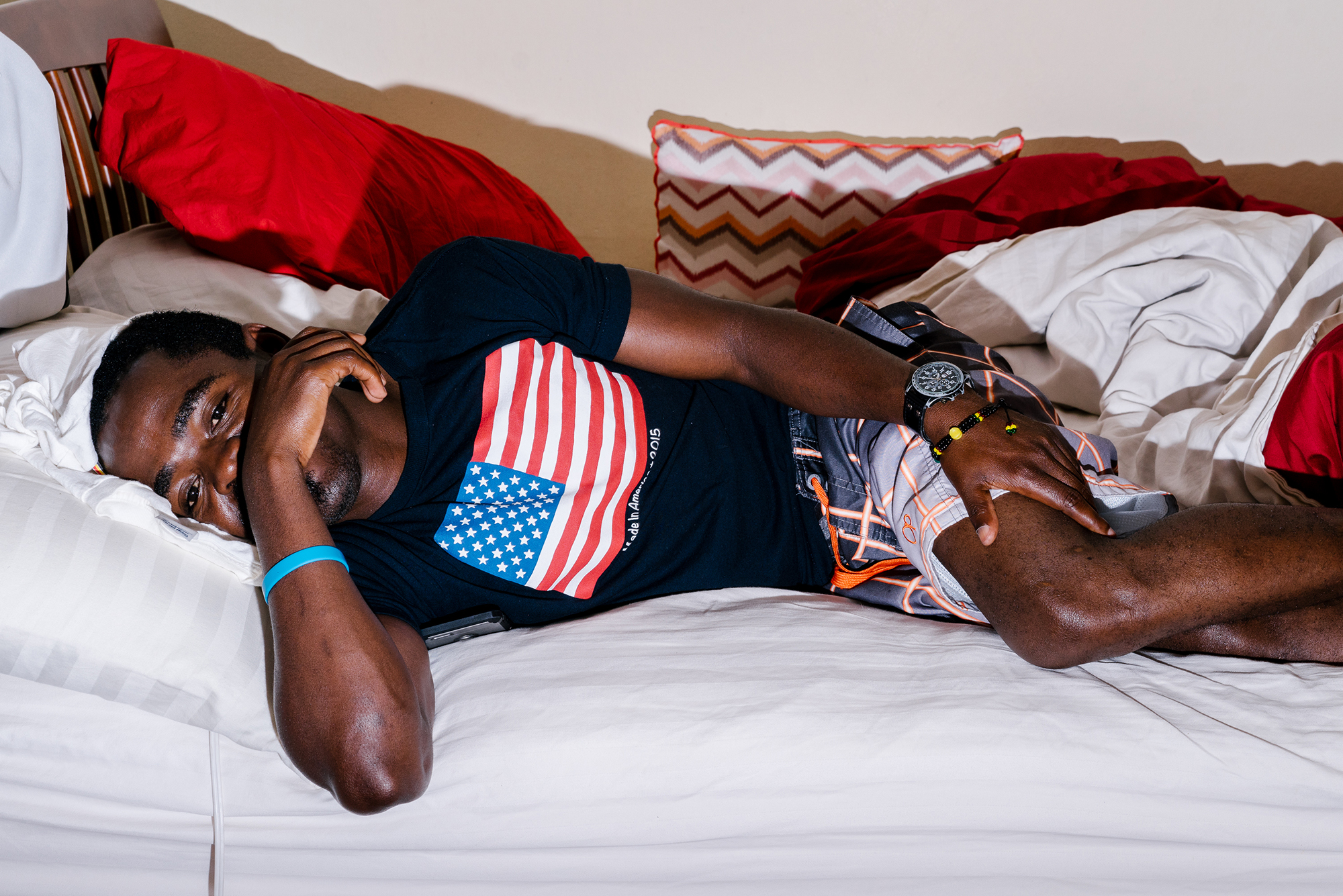 Shawn, a gay refugee from Uganda, lays in bed on Saturday, his one completely free day. He usually spends most of it catching up on sleep and doing chores. The rest of the week he works some 90 hours at two jobs, barely finding time to take a nap or do much of anything else.