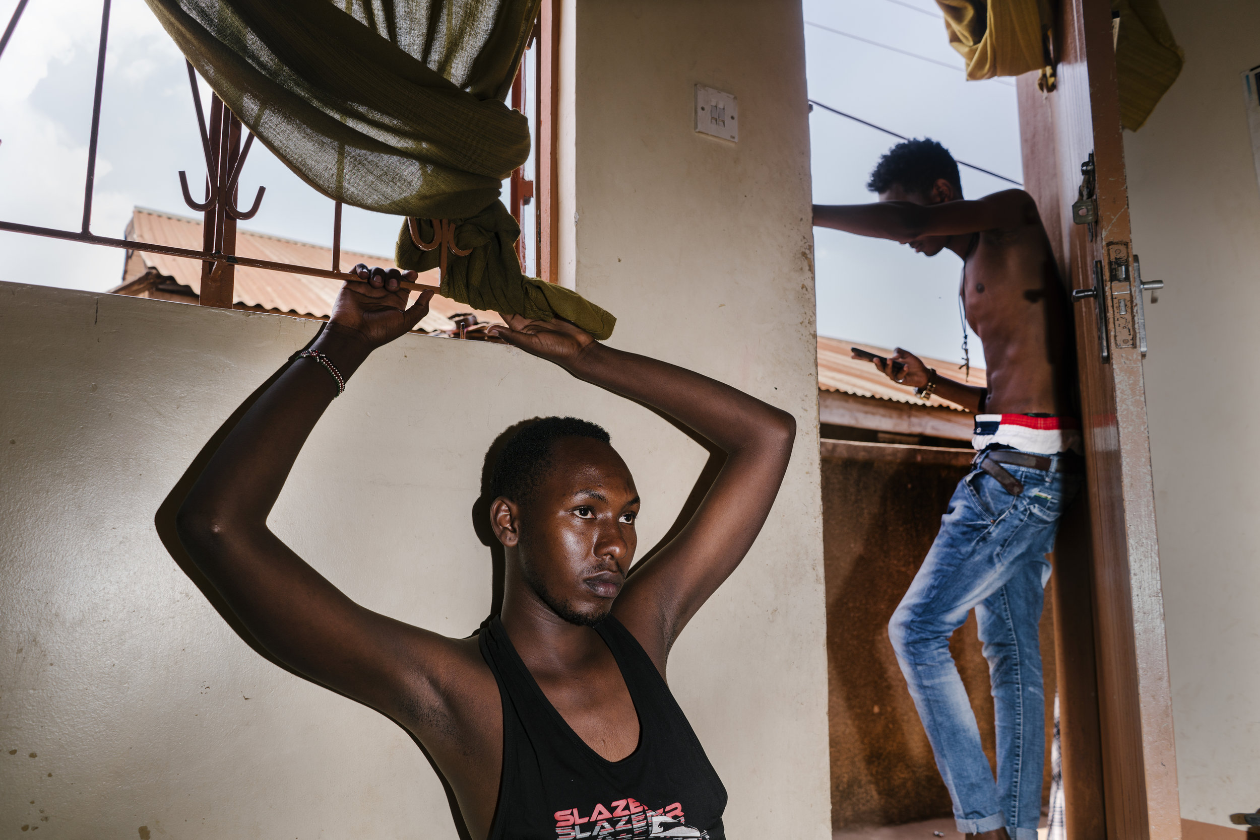 """Javan, a young transgender woman, sits in the family's living room, while her brother Shema, 18, who is bisexual, stands in the doorway. Javan spent six months in Kenya as a refugee there after a gang of men beat and stripped her naked near her home, and then forced to walk home naked while the mob chanted, """"She's a homo"""" behind her. She returned to Uganda, but now faces frequent abuse from the general public."""