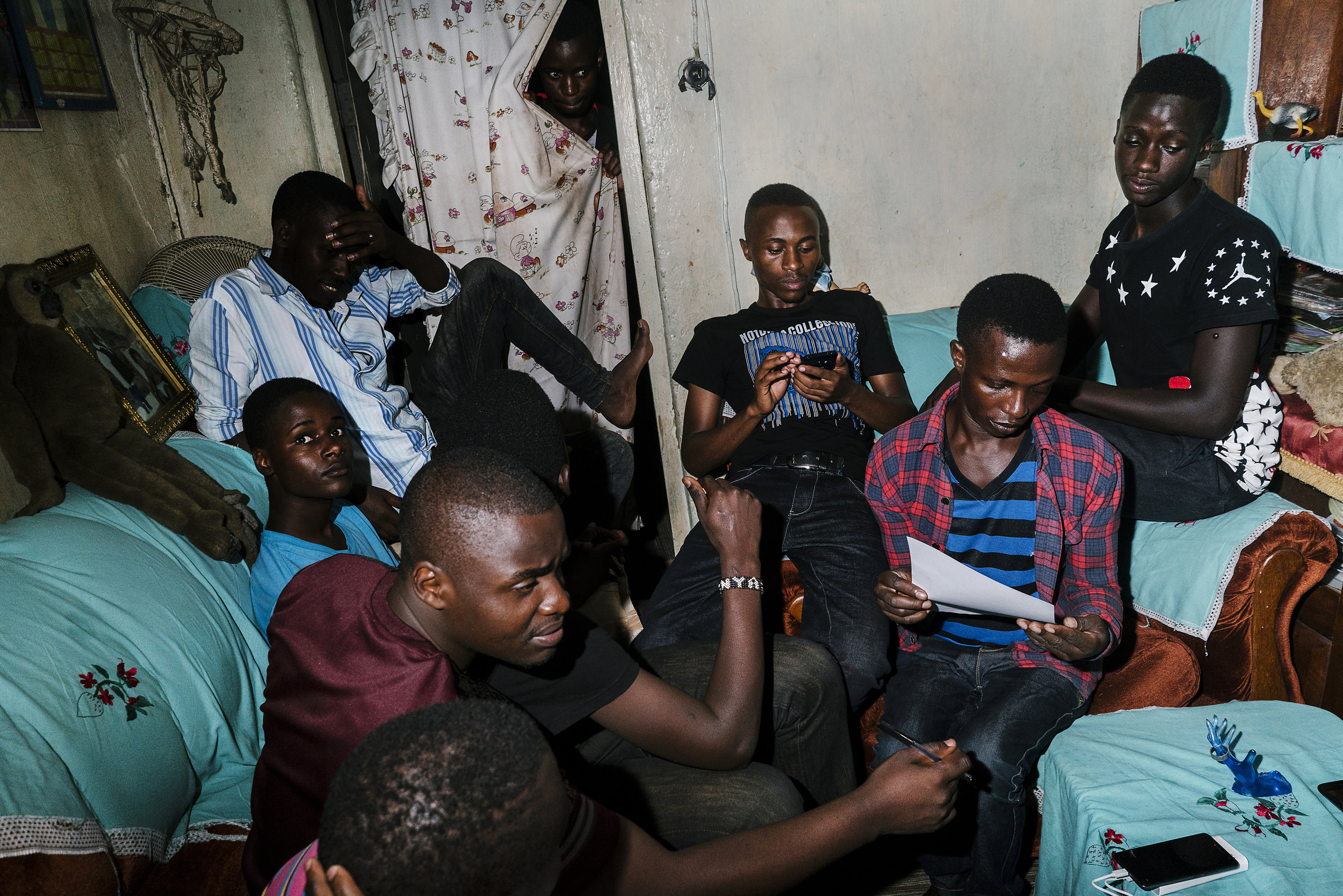 Young LGBTQ people gather in the living room of the Children of the Sun safe house. At the time this photo was taken, there were 8 people sleeping in the two room apartment, though the number fluctuates daily from six to 12. The organization had been paying the rent with earnings from a market stall, but on the day this photo was taken, the market was shut down and so the tenants resorted to sex work to pay the rent, according to one of the group's founders. Many were chased away from their families because of their LGBTQ identity, though others stay at the house for the company of others like them.