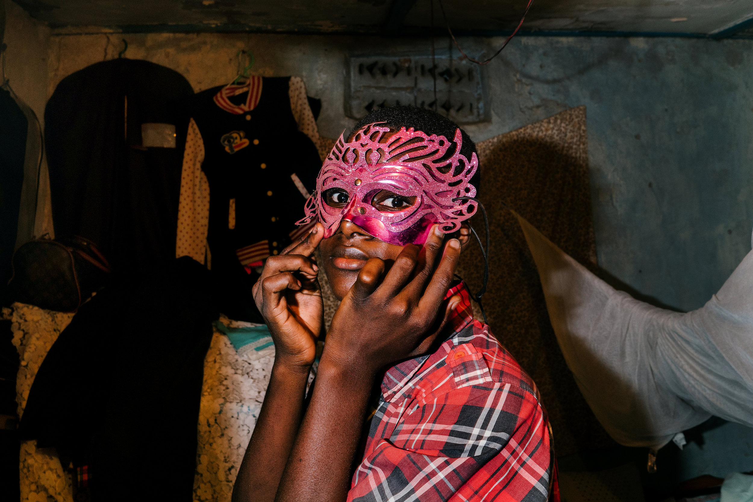 A young transgender woman poses for a portrait wearing a mask from a pride event the previous year. She was kicked out of her home after her parents found out she was trans. She found shelter and camaraderie at the Children of the Sun safe house.