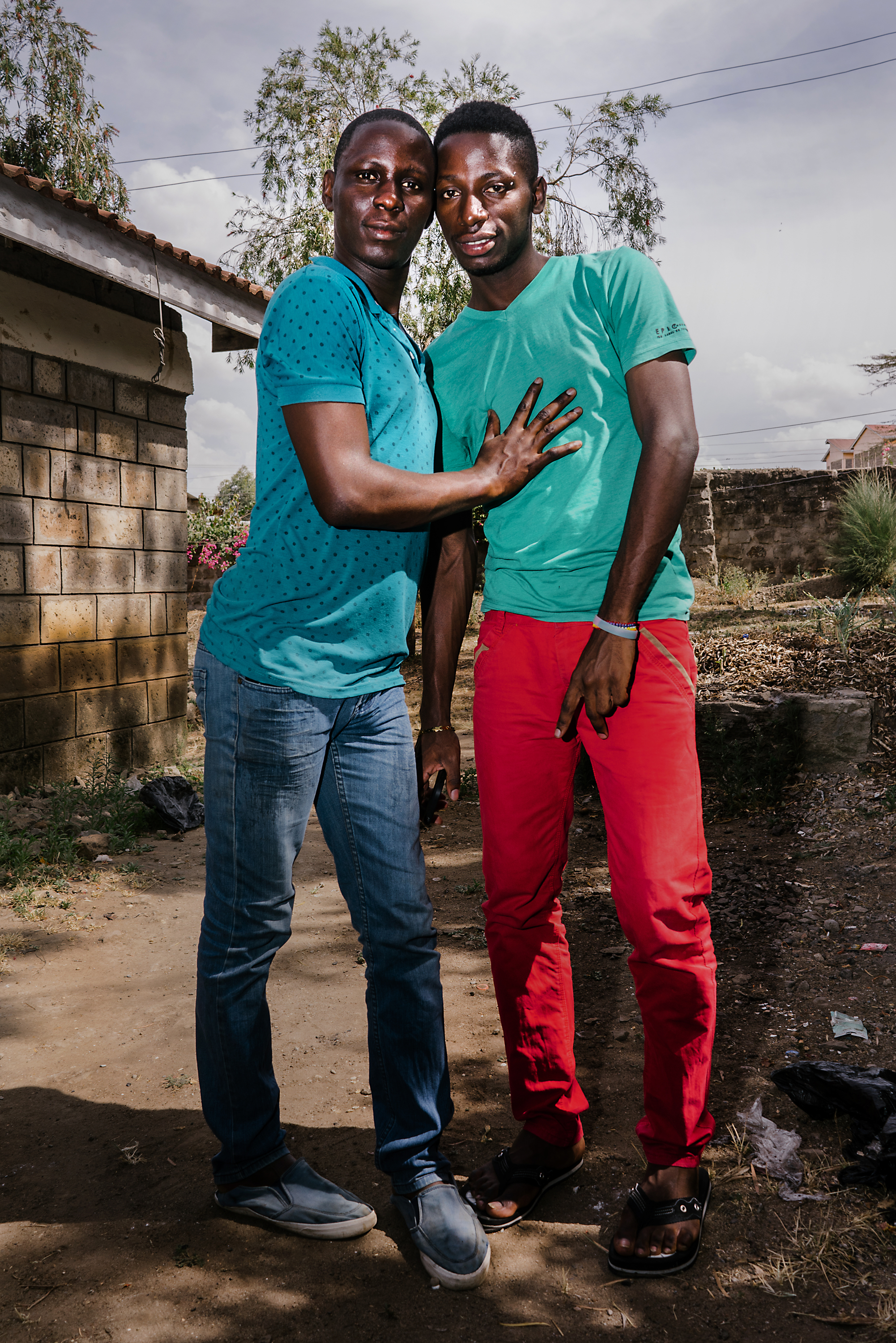 J. and Y., both LGBTQ refugees from Uganda, pose for a portrait outside the home they lived in in a town just outside of Nairobi, Kenya. More than a dozen LGBTQ refugees from Uganda had gathered together in this house for safety and camaraderie, but after a few months, the house had to be evacuated due to threats from neighbors and the police, according to residents of the house.